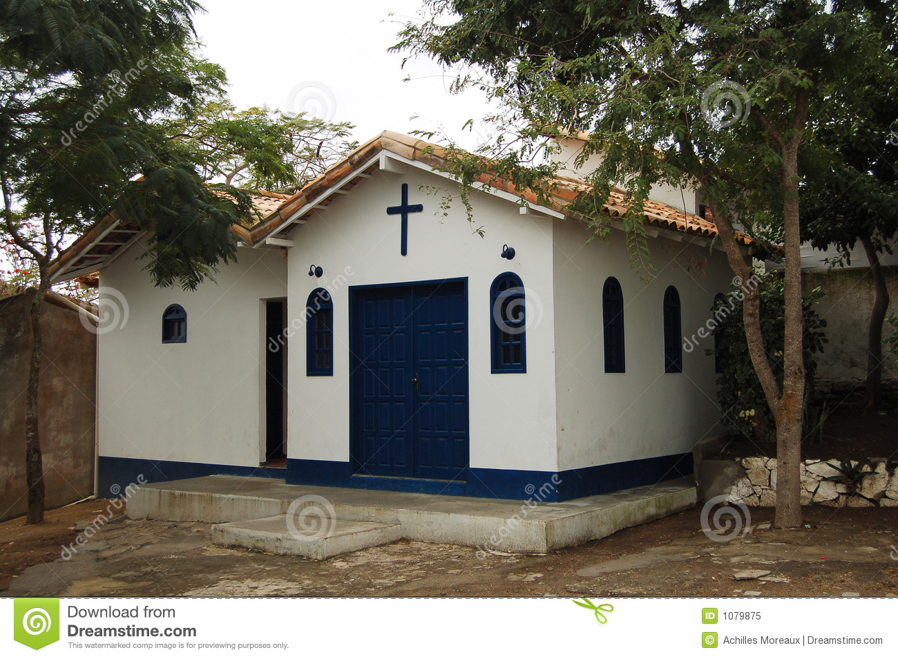 Exterior of small church building with cross above door.