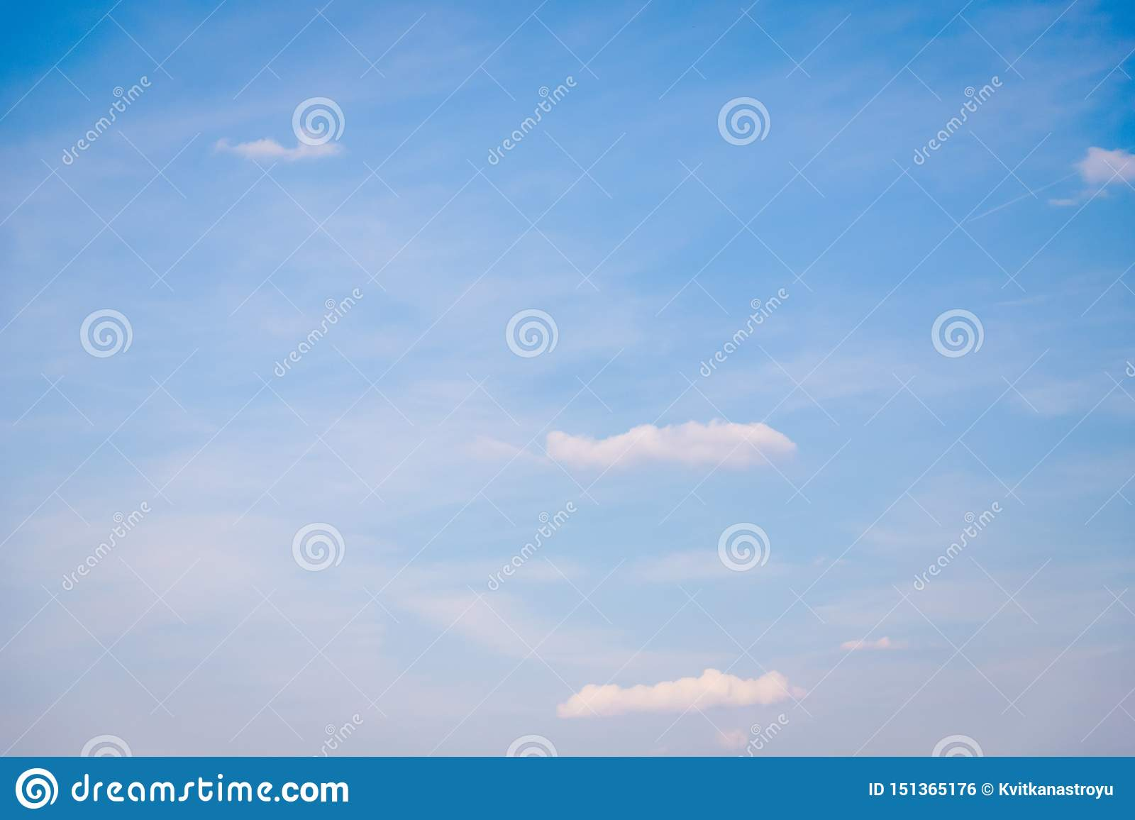 Small clouds on a light blue sky background, soft color