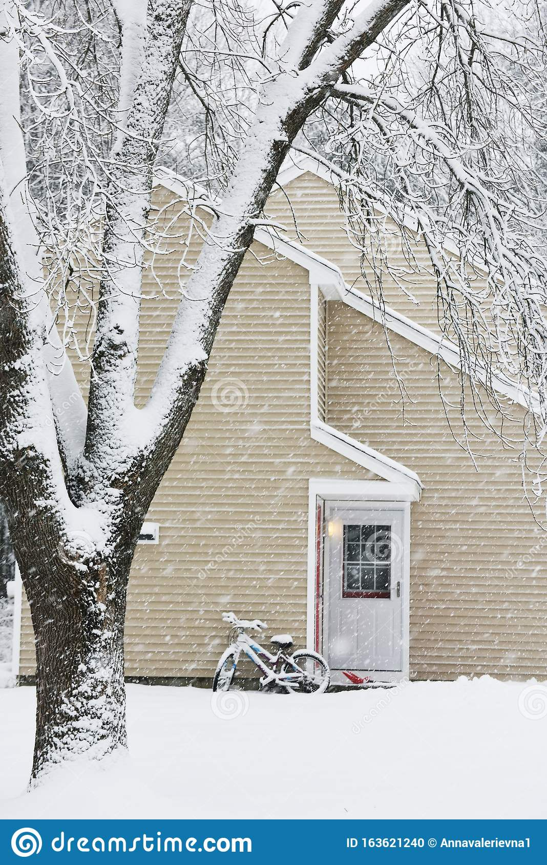 A Small Cozy House Covered With Snow During A Snowfall The