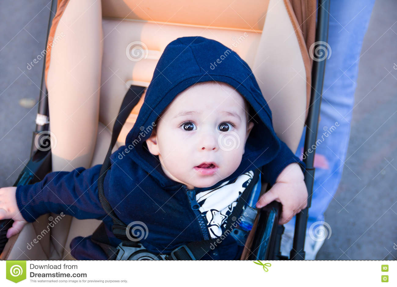 small cute newborn baby boy sitting in a carriage in warm winter