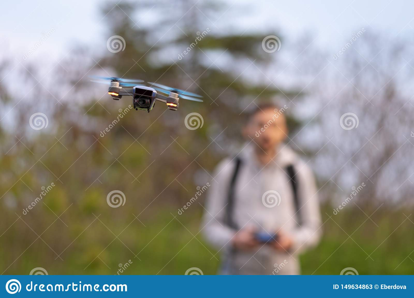 Young man navigates small drone.
