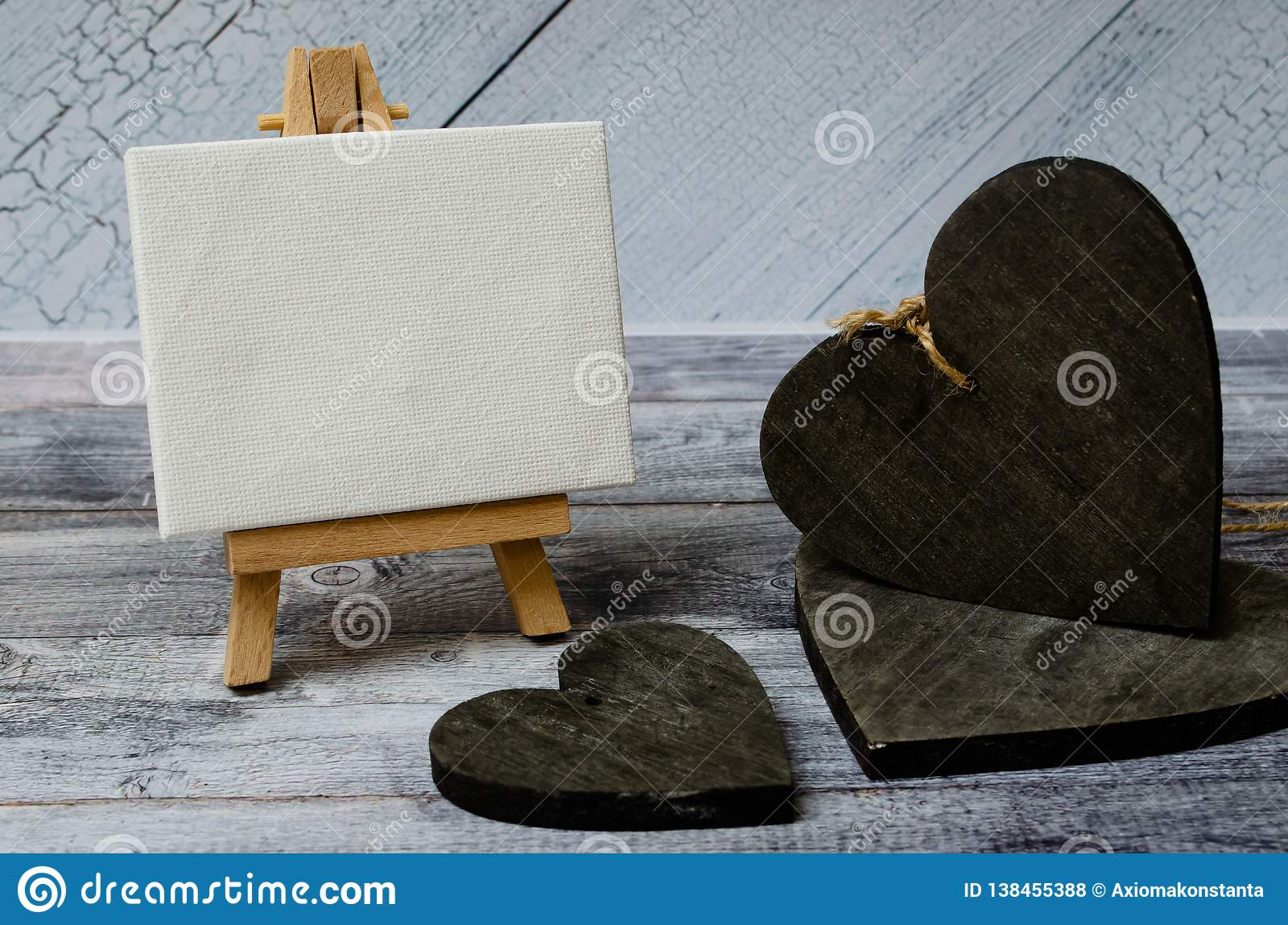 Small easel with a blank canvas over white and three dark wooden hearts. Old wooden background and big copy space for
