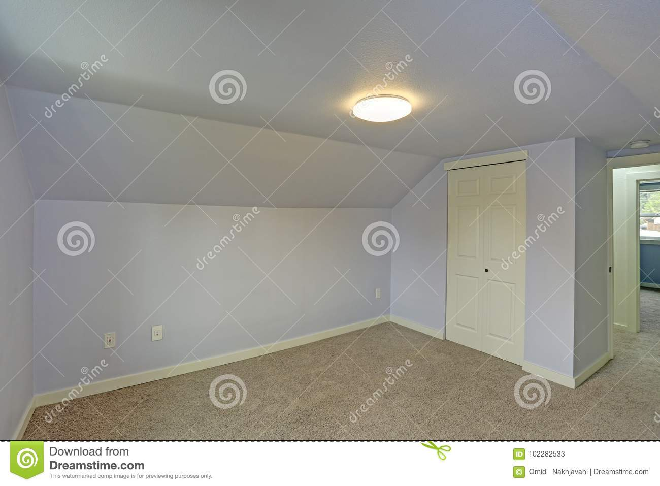 Small Empty Blue Bedroom Accented With Vaulted Ceiling Stock Image