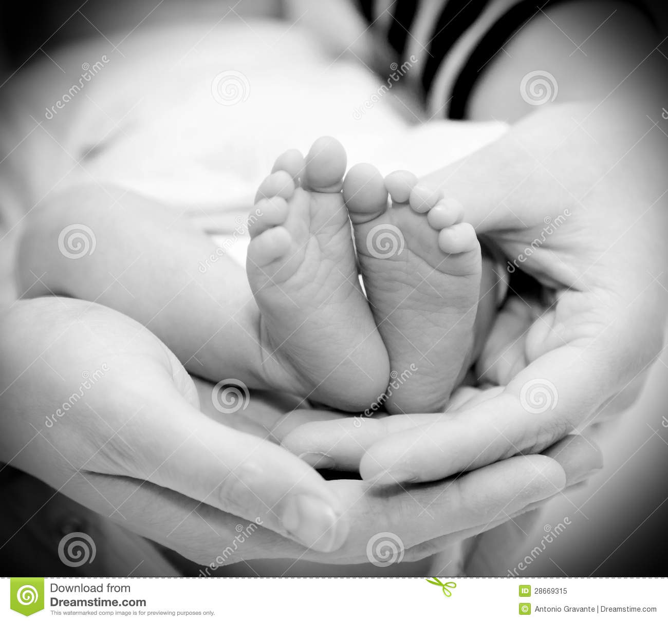 Small feet baby holds his mother in her hands