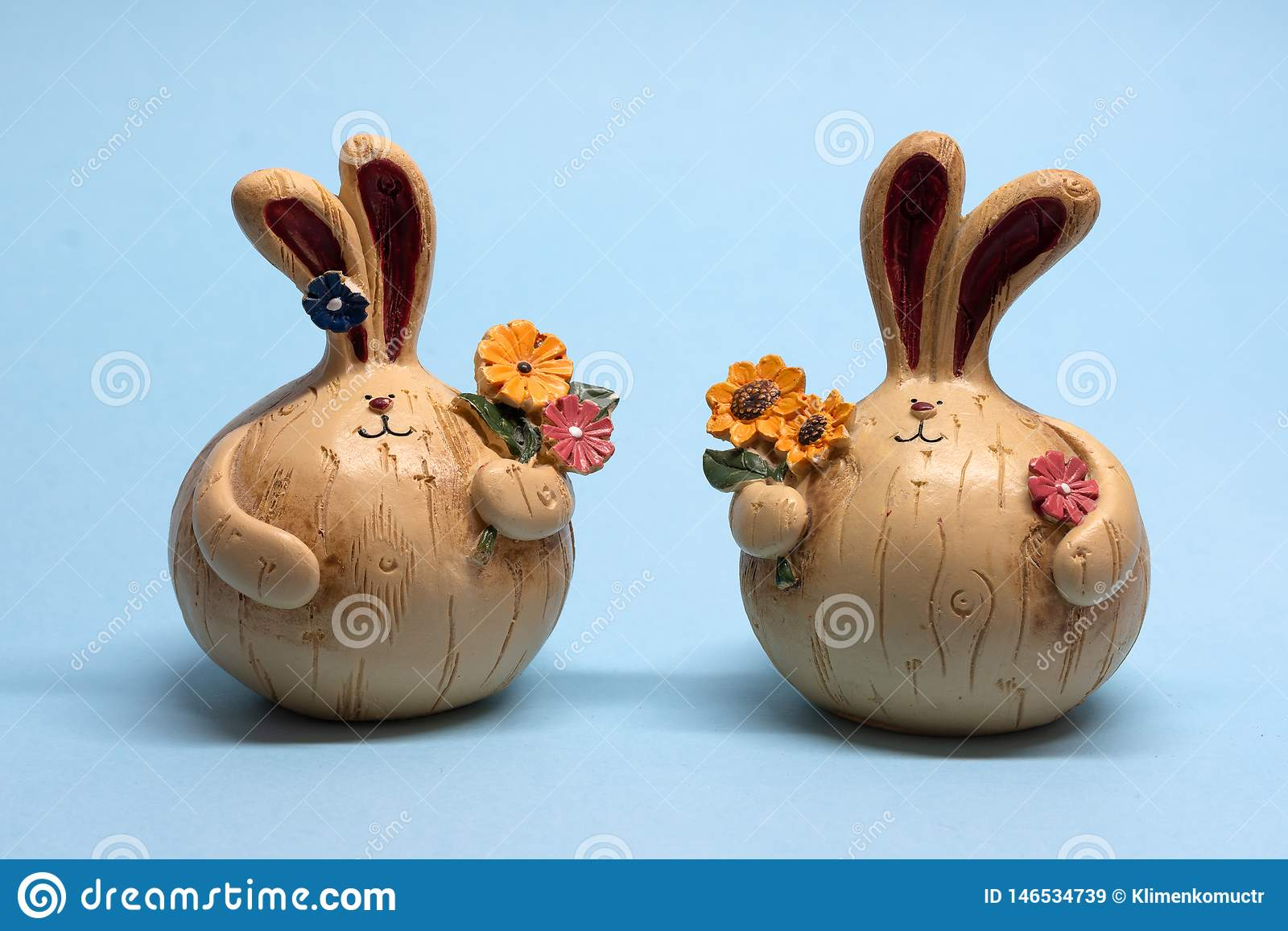 Small figures of two hares with flowers on a blue background