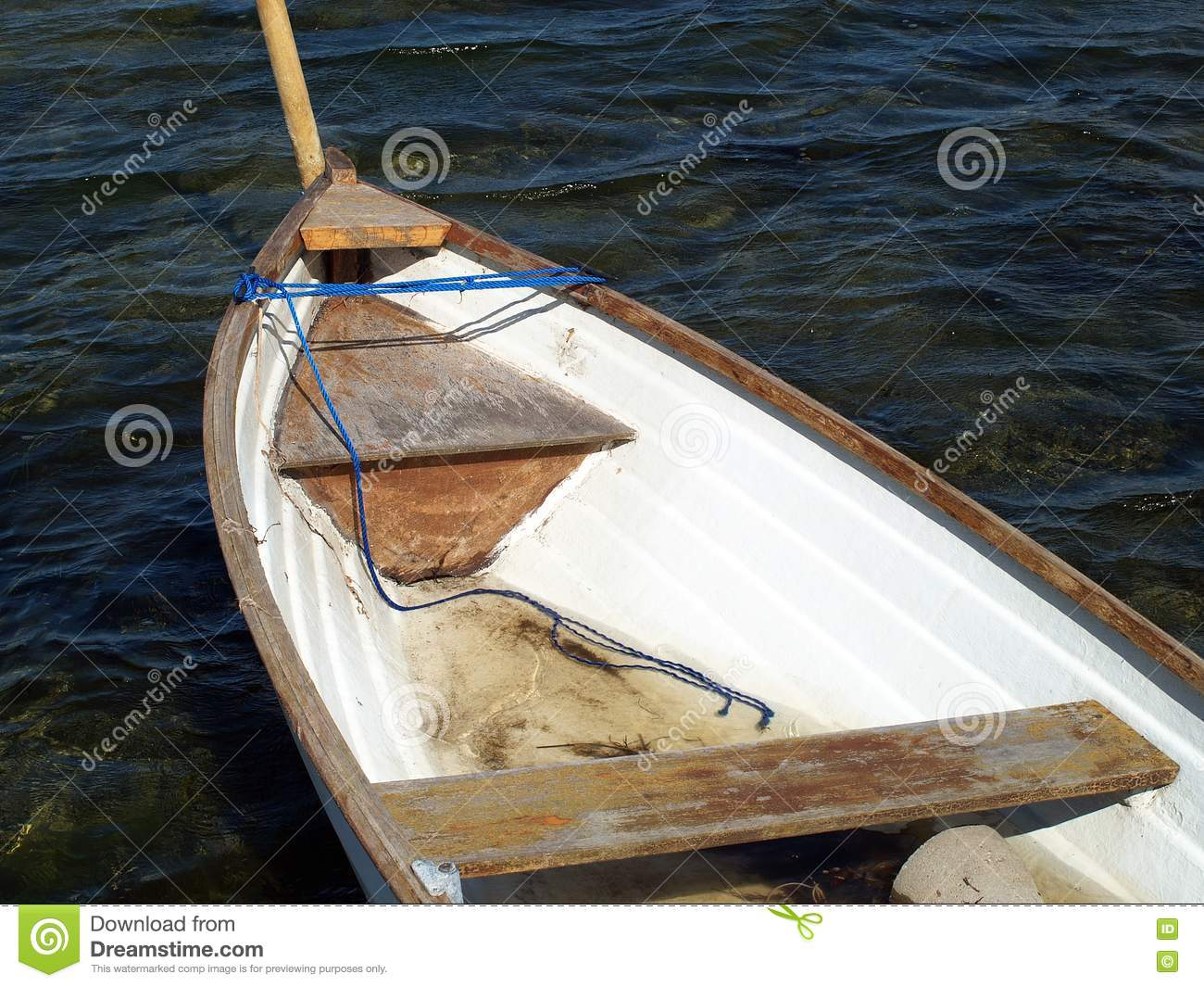 Small classical wooden fishing boat dory rowboat floating on sea water ...