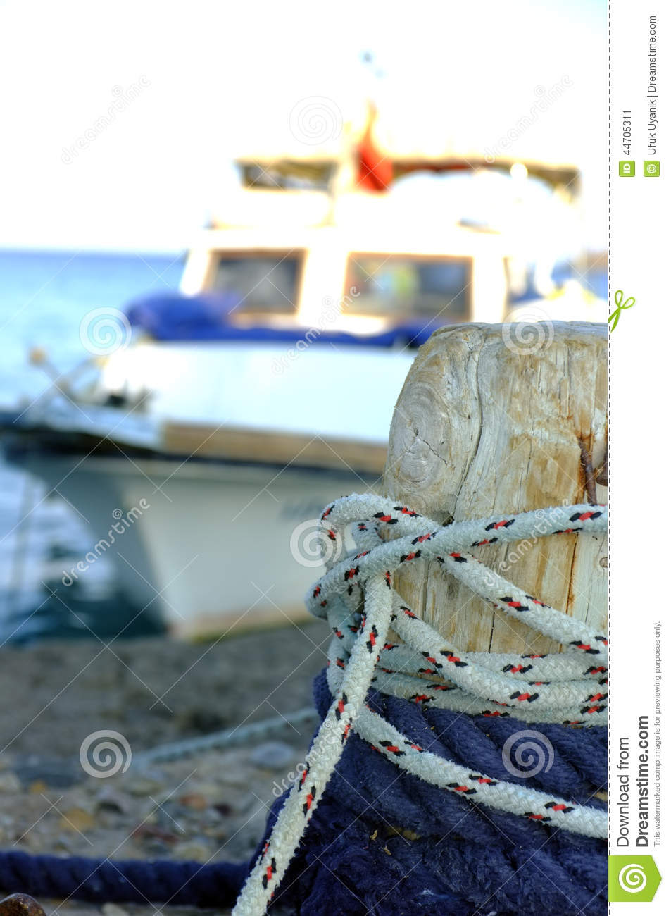 Small Cement Pole : Small fishing boat moored to wooden pole stock photo