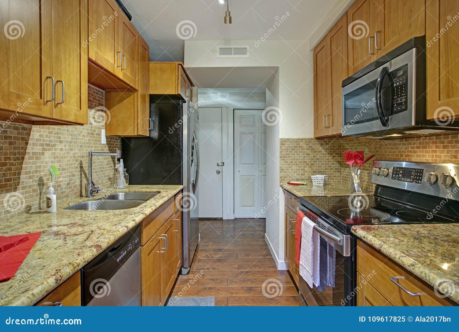 Small Galley Kitchen Design With Black Kitchen Appliances Stock ...