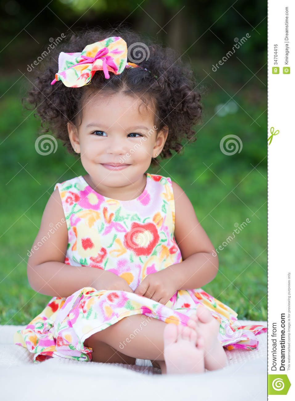 Small Girl With An Afro Hairstyle Sitting On The Grass Stock Photo - Hairstyle small girl