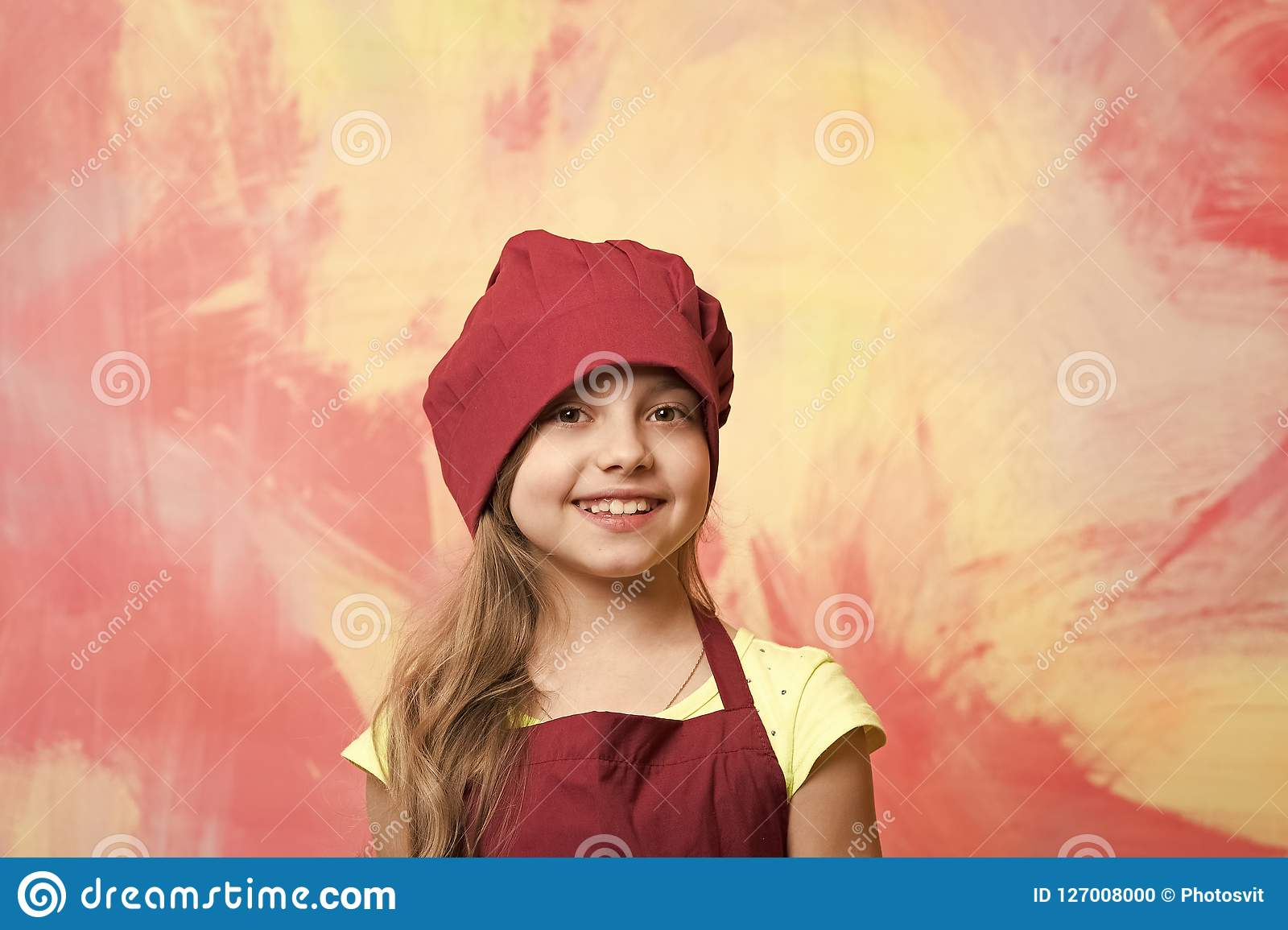 43c86c034ef Small baby girl or cute child with happy face in red chef hat and cook apron  on colorful abstract background