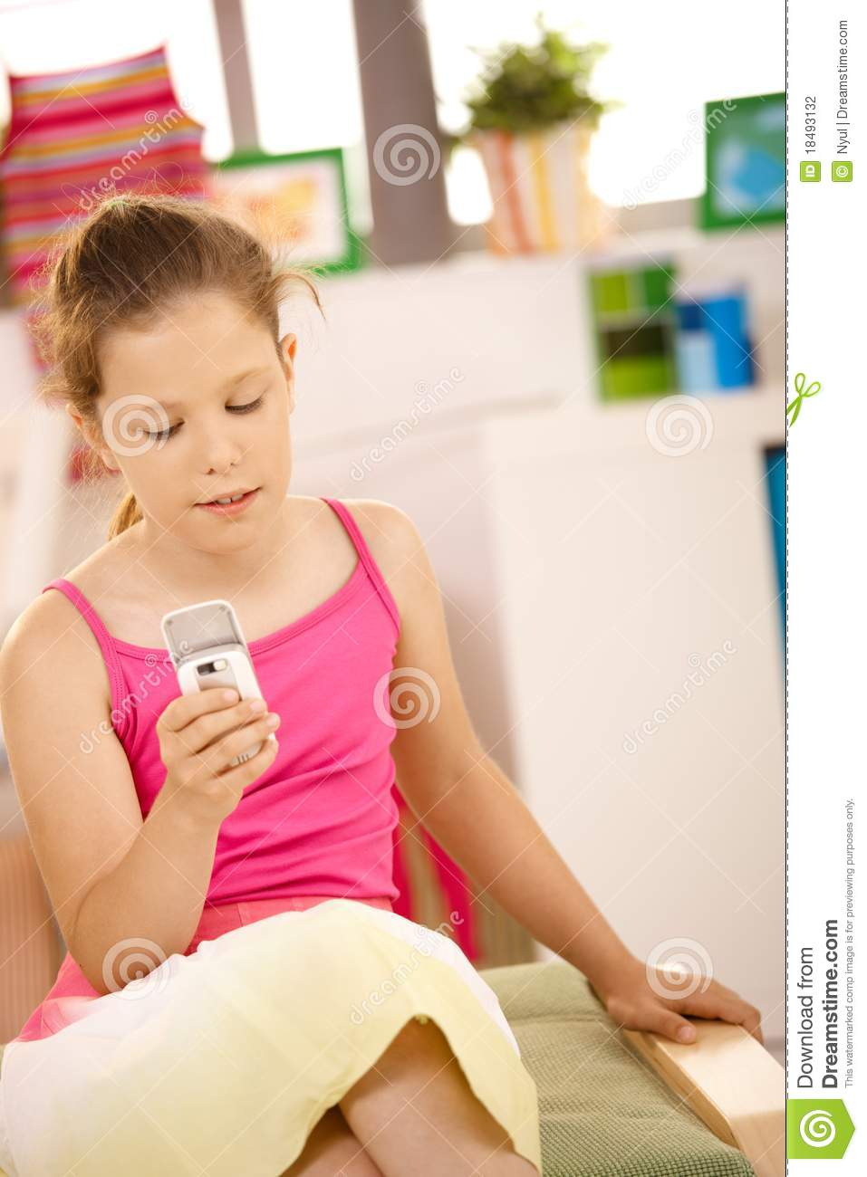 Small girl texting on phone at home
