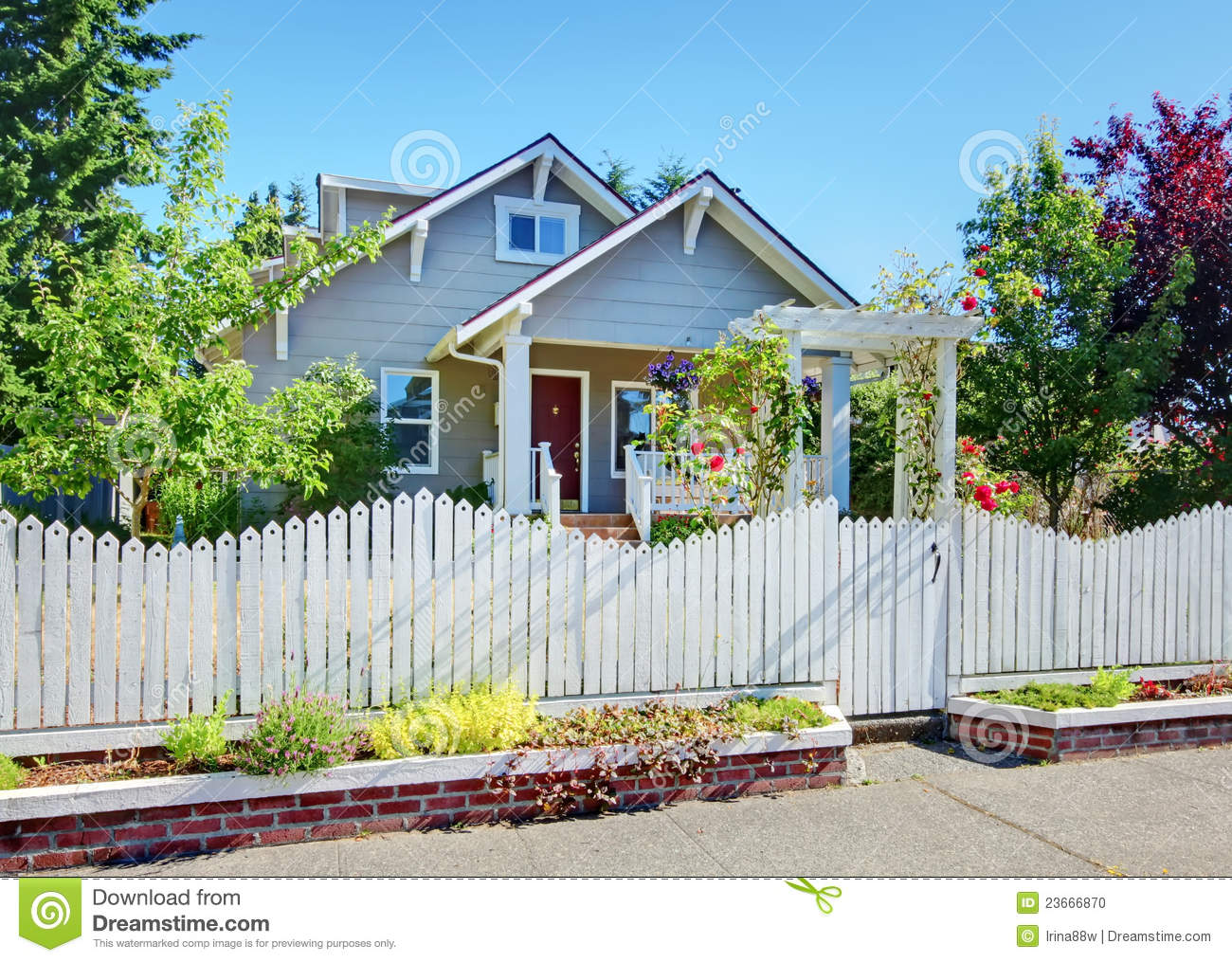 Red entrance door in front of residential house stock photo - Small Grey Craftsman Style Home Behind White Fence Stock