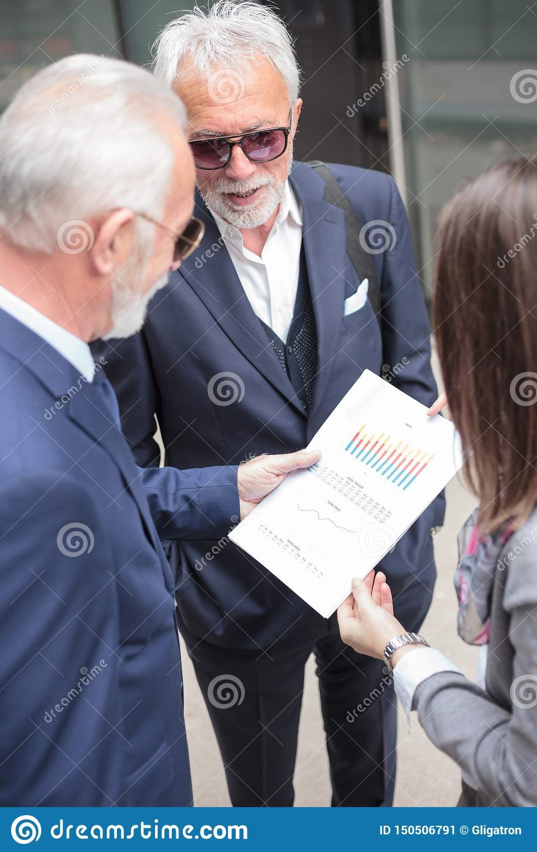 Small group of business people meeting in the street outside of an office building, looking at sales reports