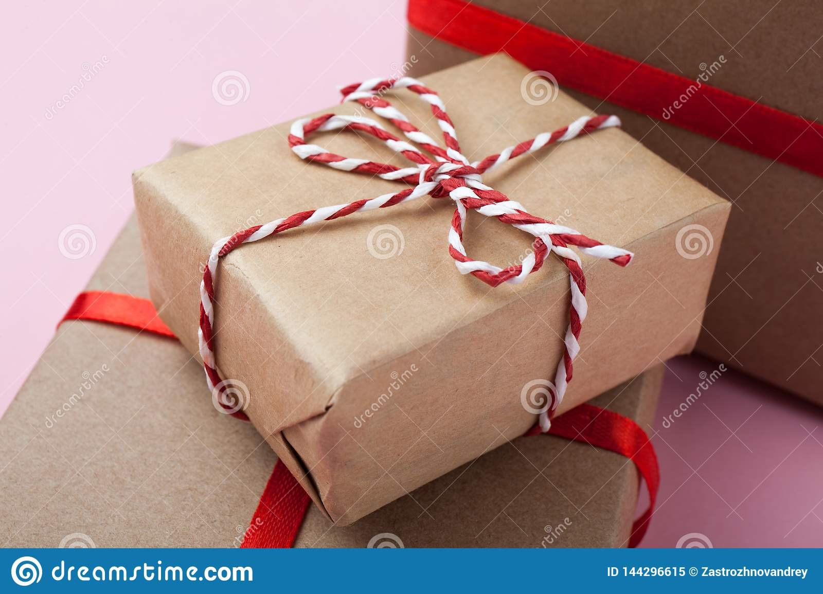 Small Handmade Gift Boxes With A Red Ribbon On A Pink Background