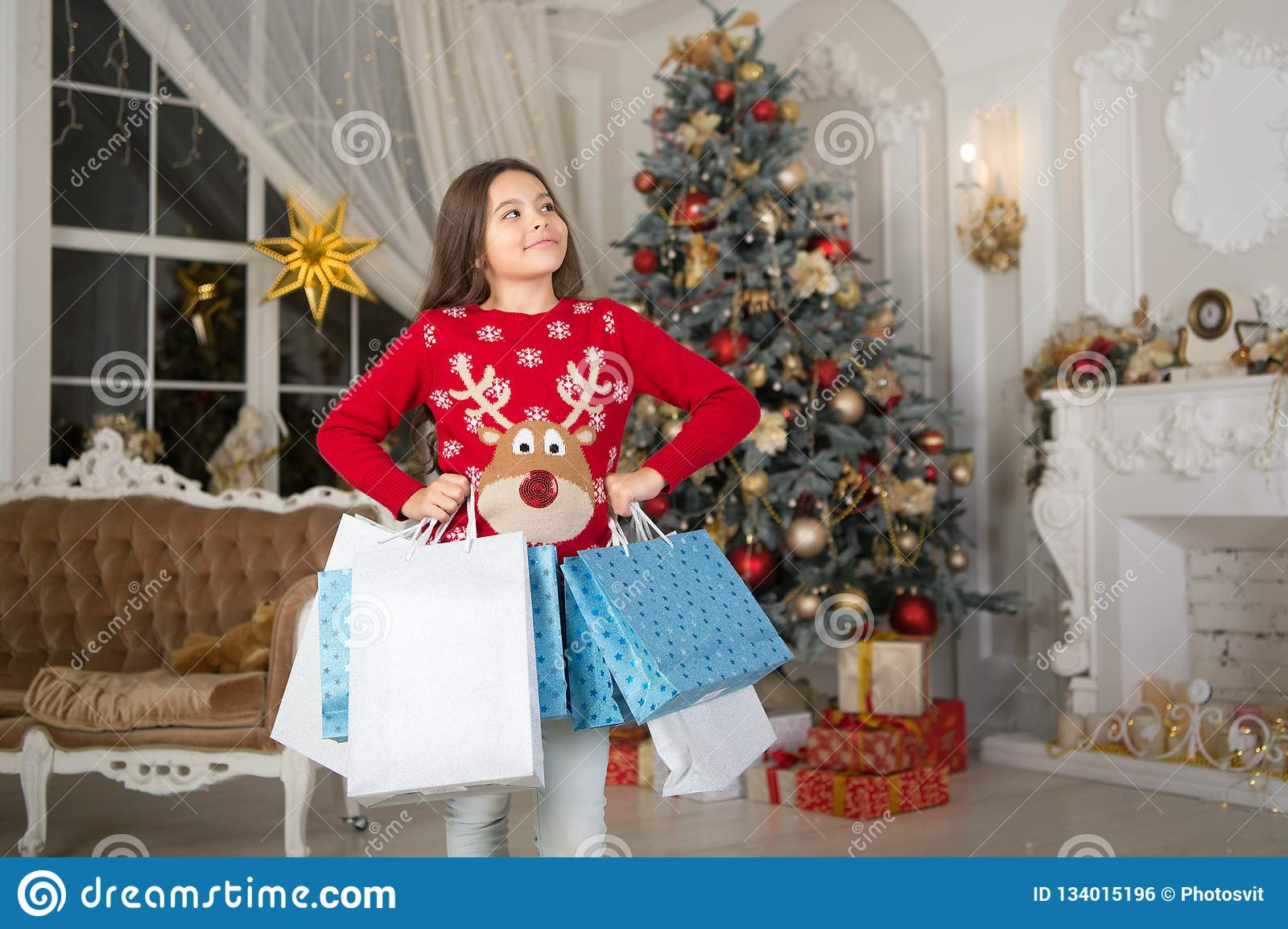 Small happy girl at christmas. Christmas. Kid enjoy the holiday. Happy new year. girl with shopping bags. morning before