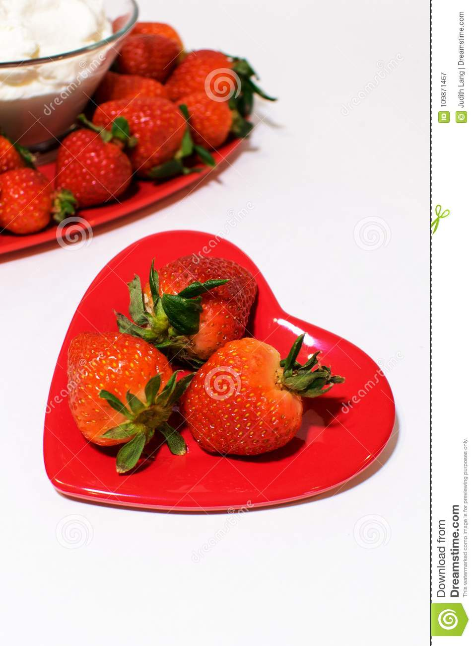 Small heart plate in front with strawberries bigger one behind.