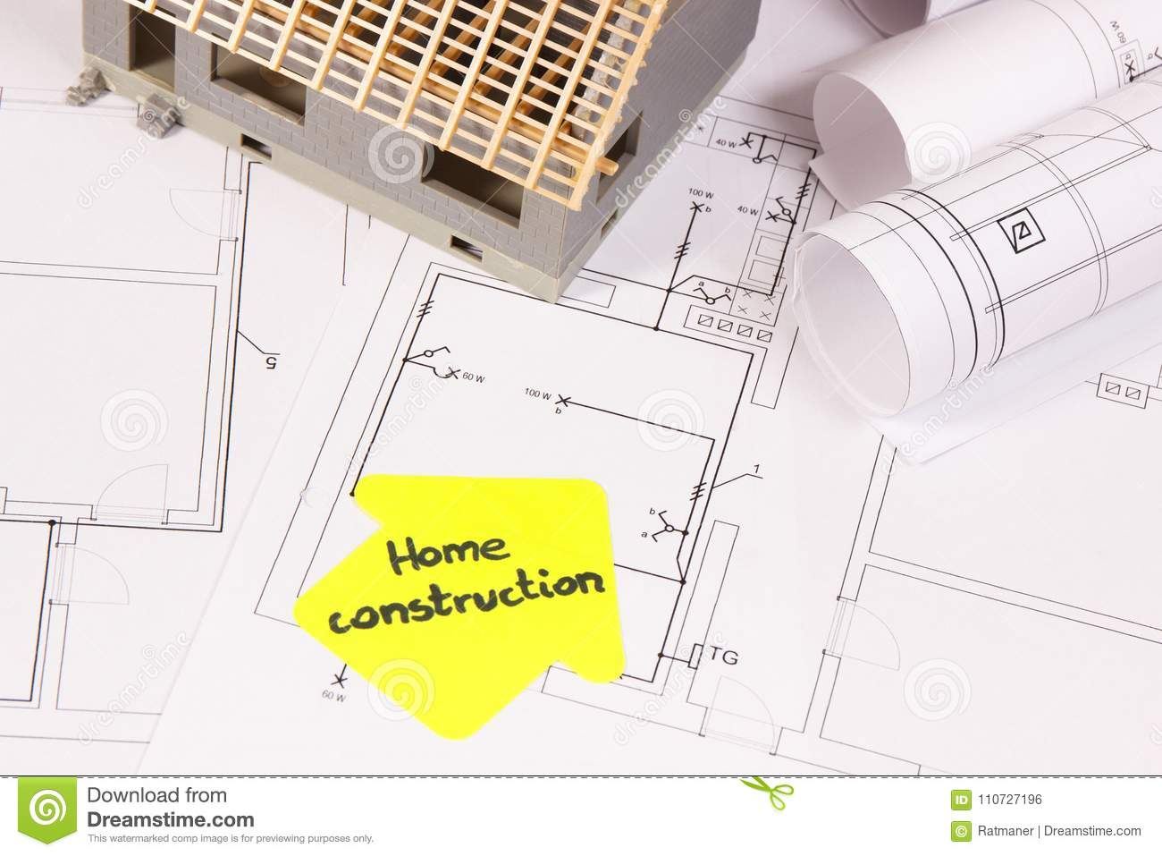 Small House Under Construction And Rolls Of Electrical Diagrams Or