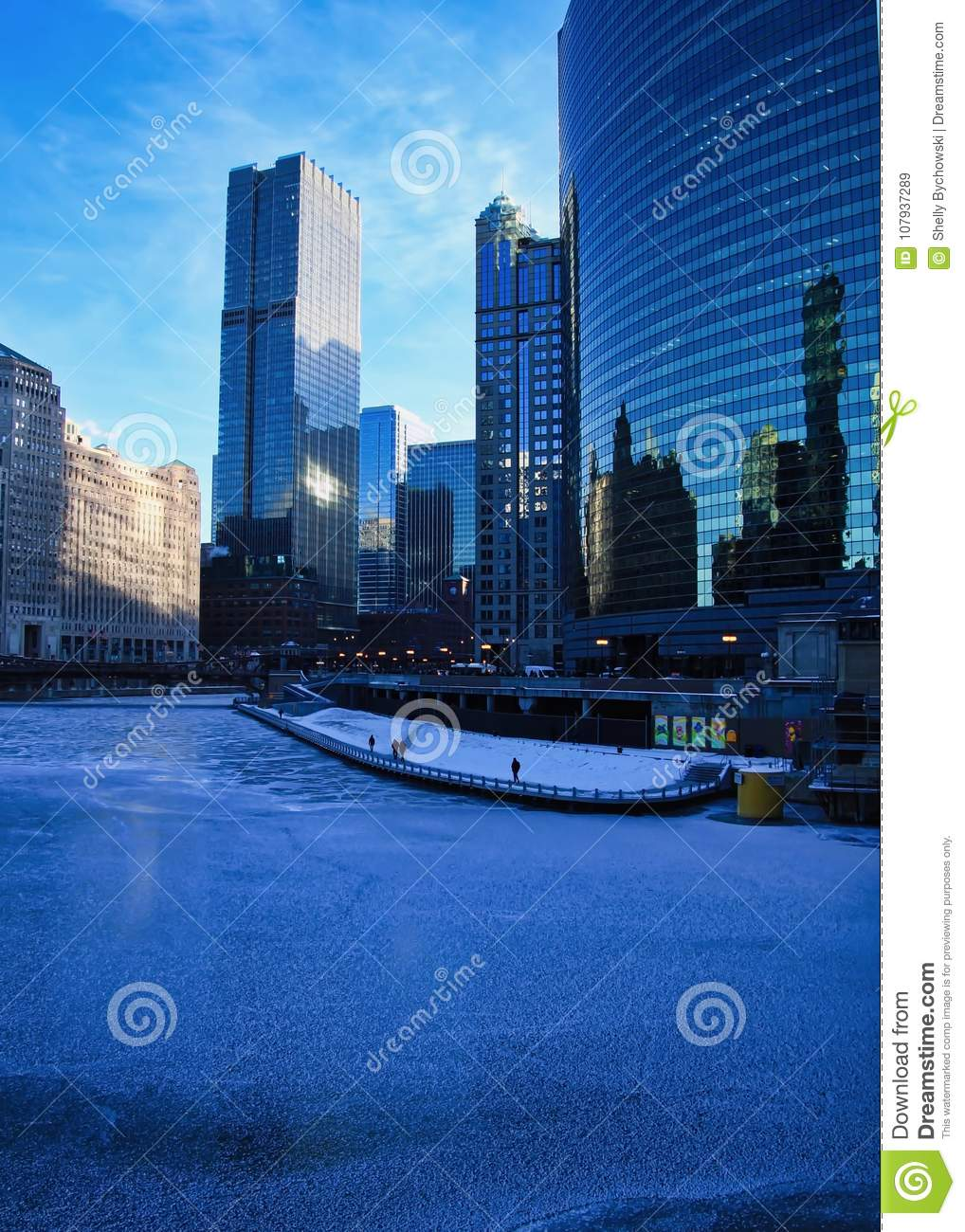 High-angle view of pedestrians on the riverwalk alongside a frozen Chicago River on a blue, frigid morning in winter.