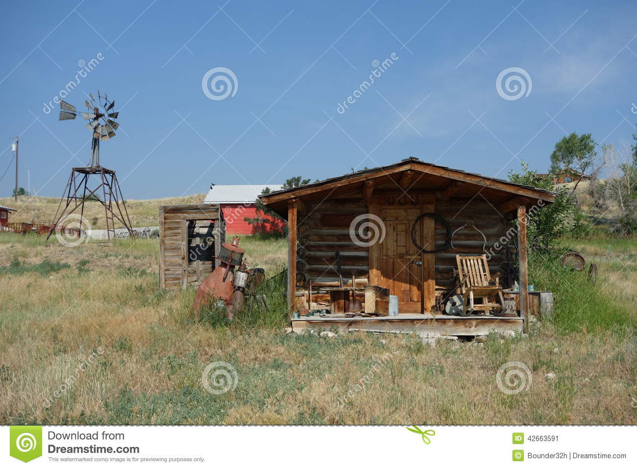 A Small Log Cabin With A Windmill In Idaho Stock Photo