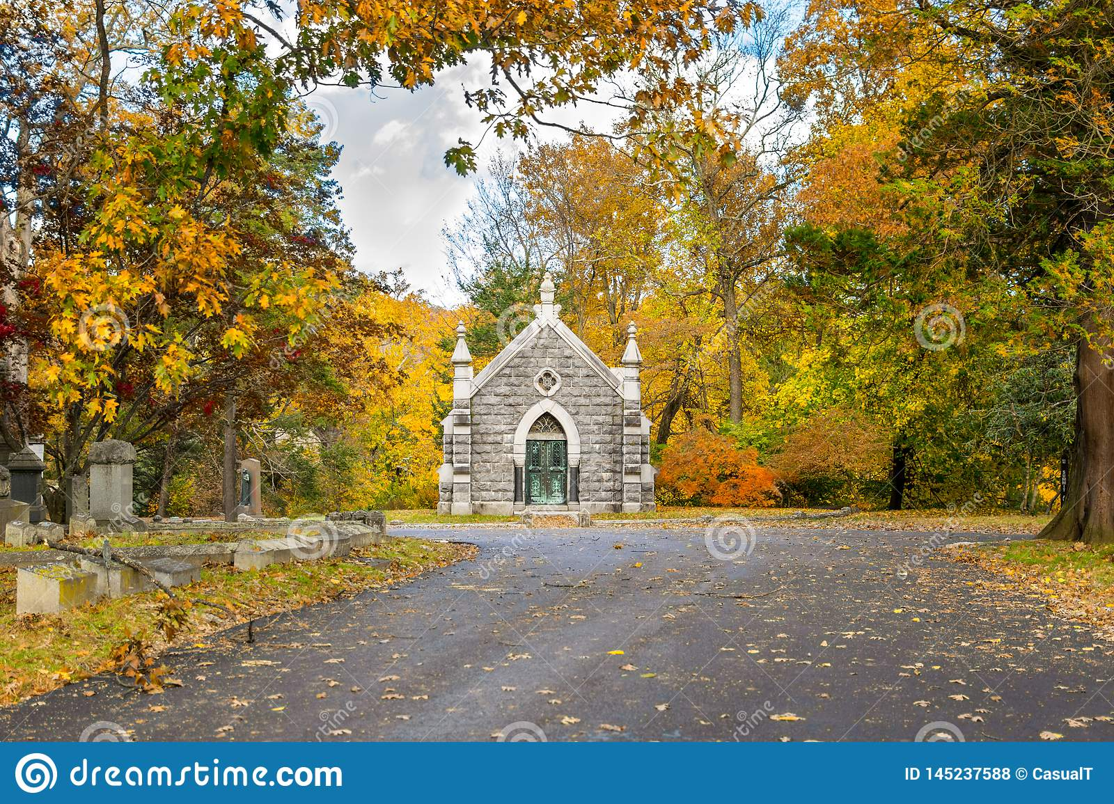 Small mausoleum at Sleepy Hollow Cemetery, surrounded by autumnal fall foliage, Upstate New York, NY, USA