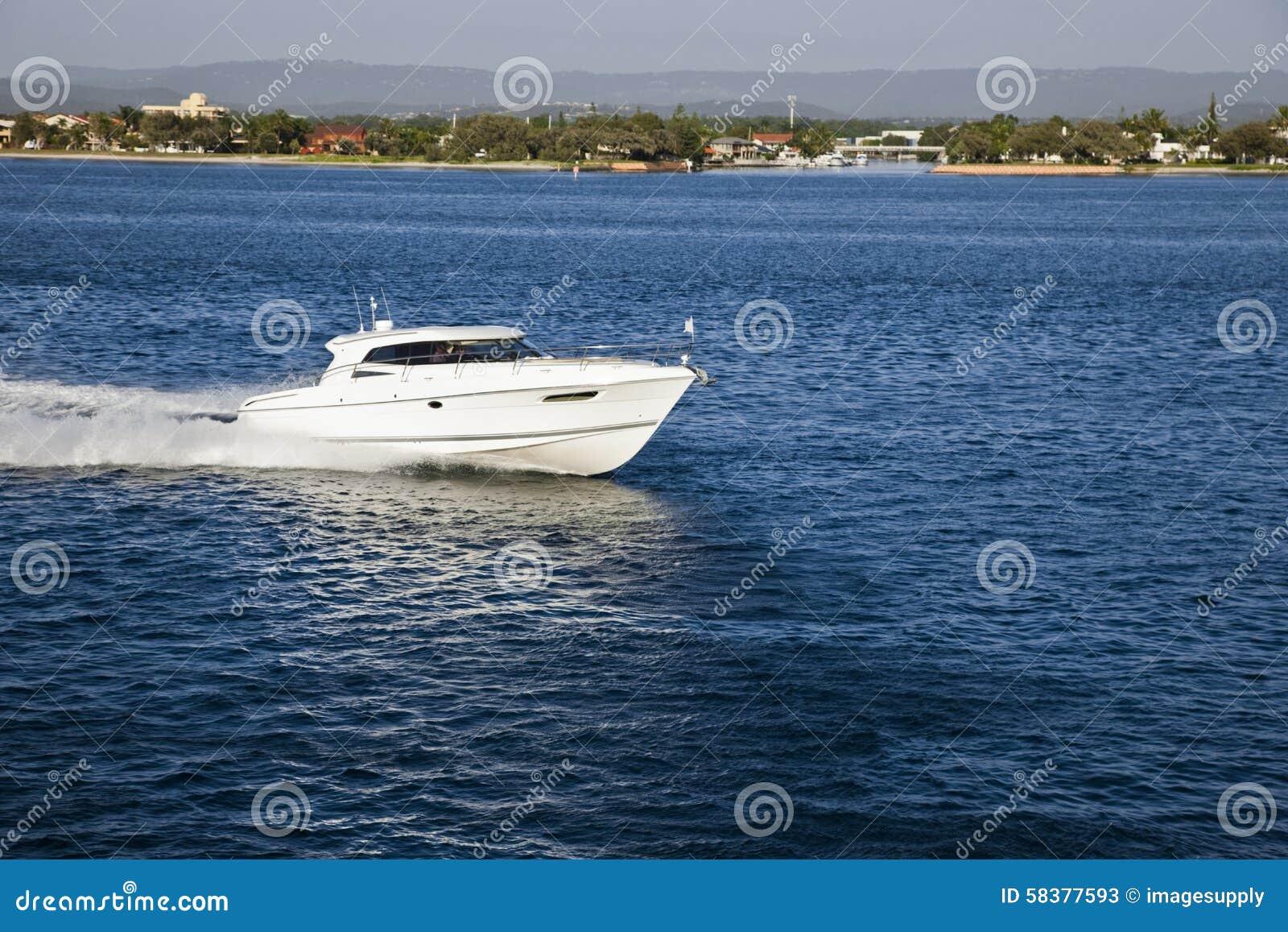 A Small Motor Boat Sailing Close To The Coast Stock Photo