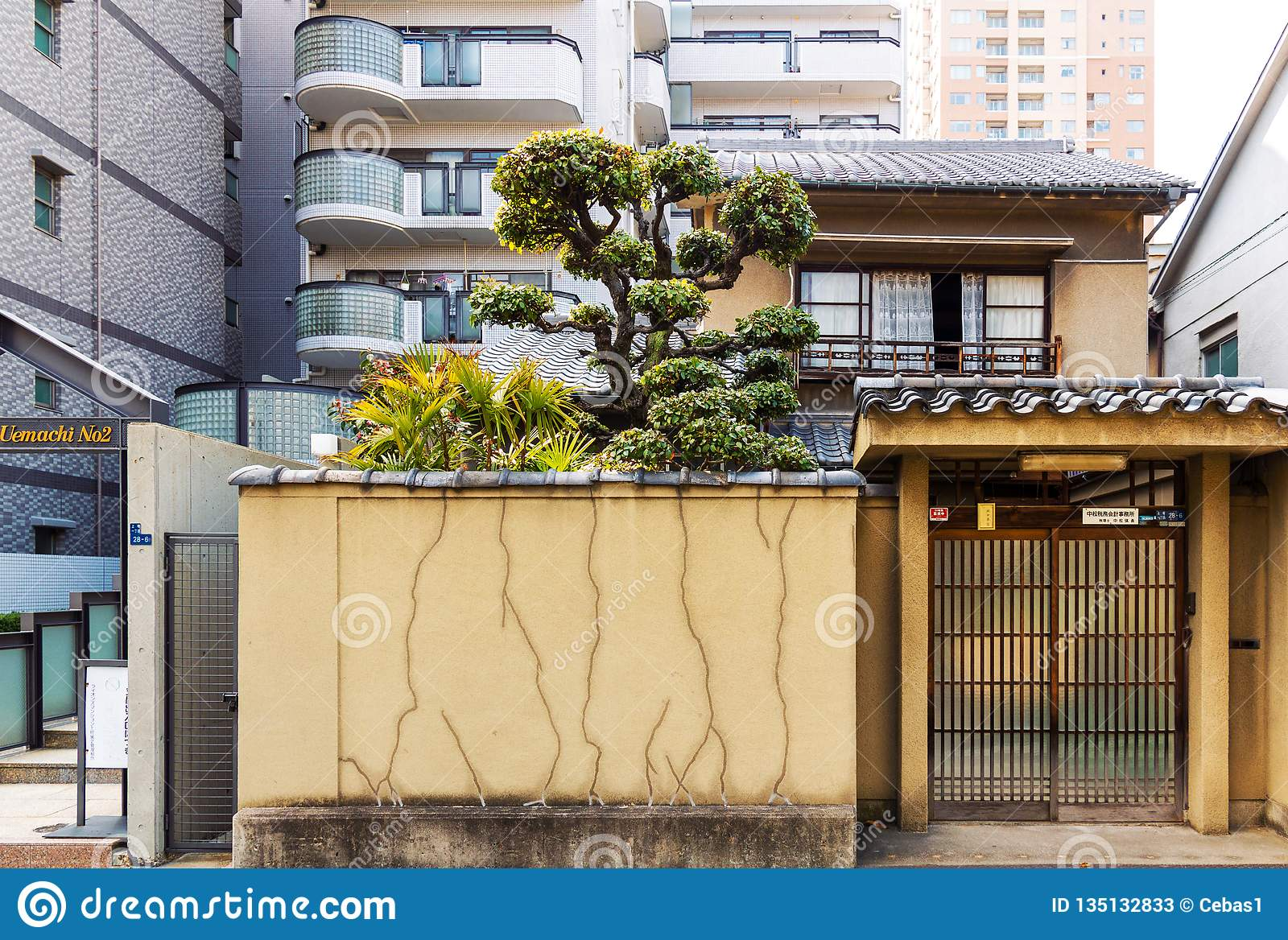 Small old japanese house facade in the background of high residential buildings in Japan