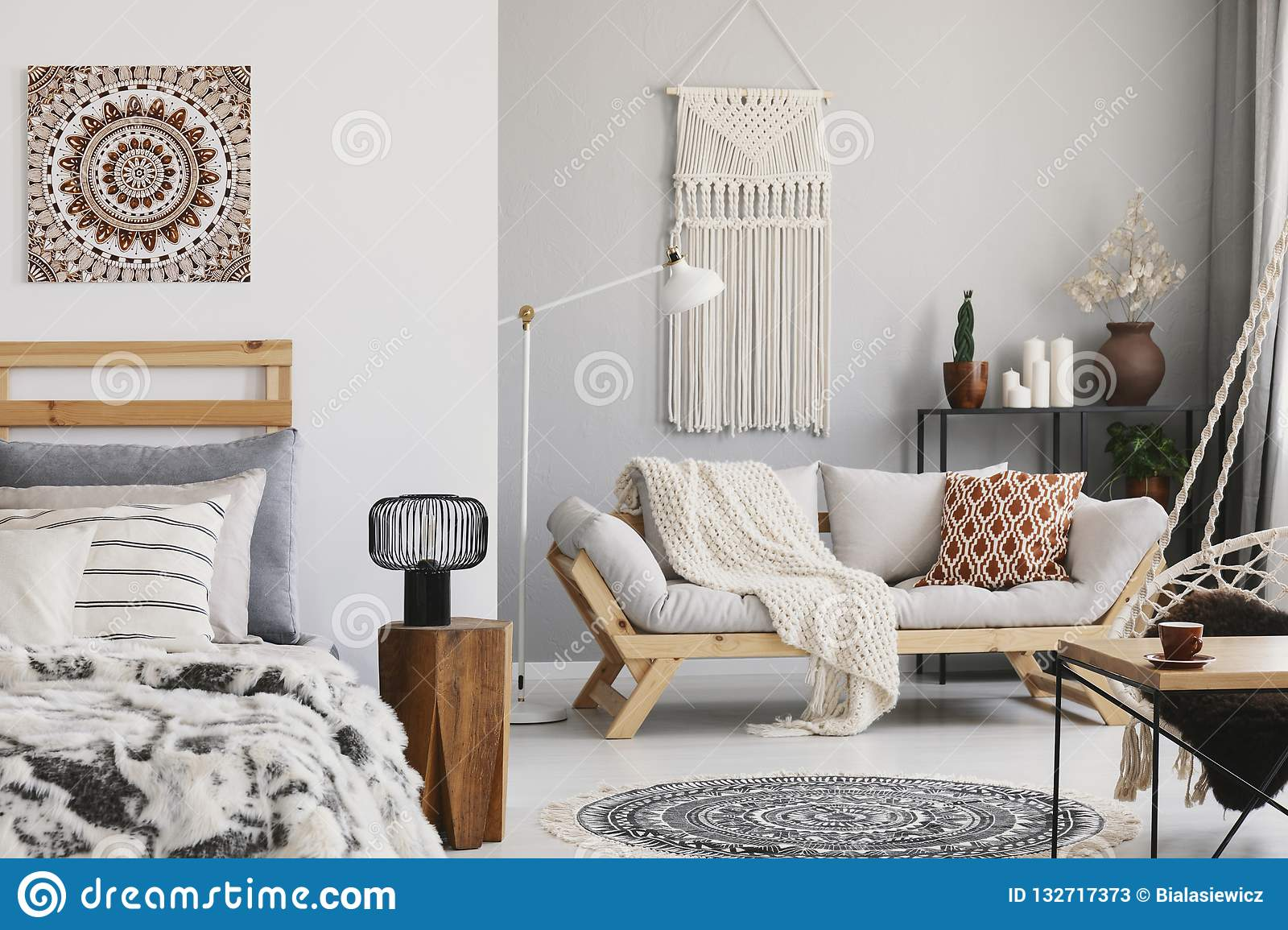 Small open space flat interior with beige sofa with cushion macrame on the wall