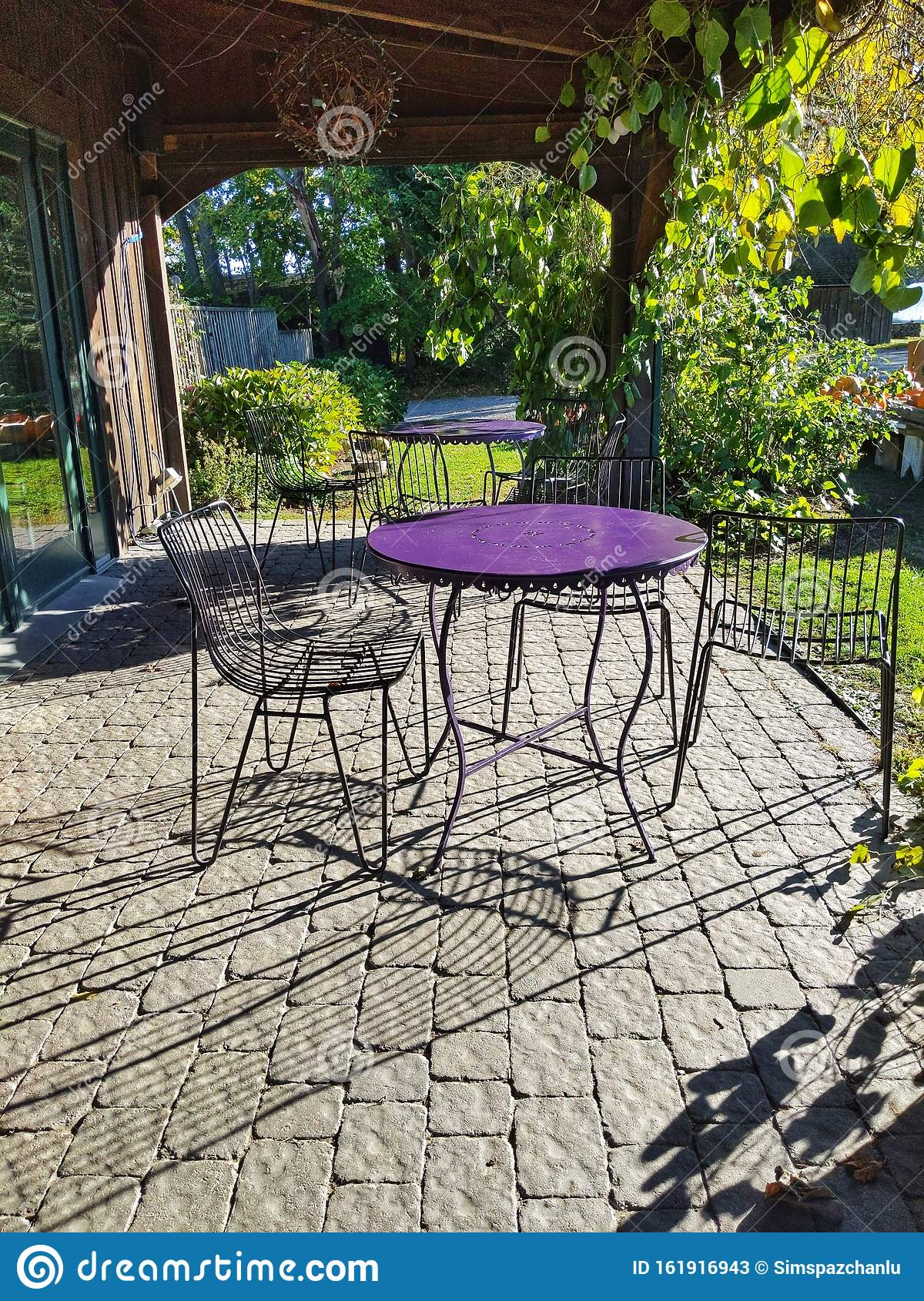 Picture of: Dining Alfresco With Purple And Black Iron Table And Chairs Stock Image Image Of Gold Forest 161916943