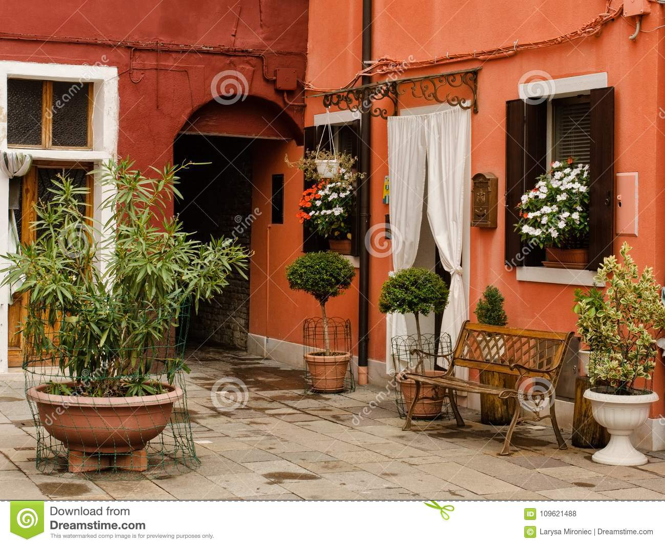 small patio of the brightly painted houses in burano, italy stocksmall patio of the brightly painted houses decorated with flowers in burano in northern italy