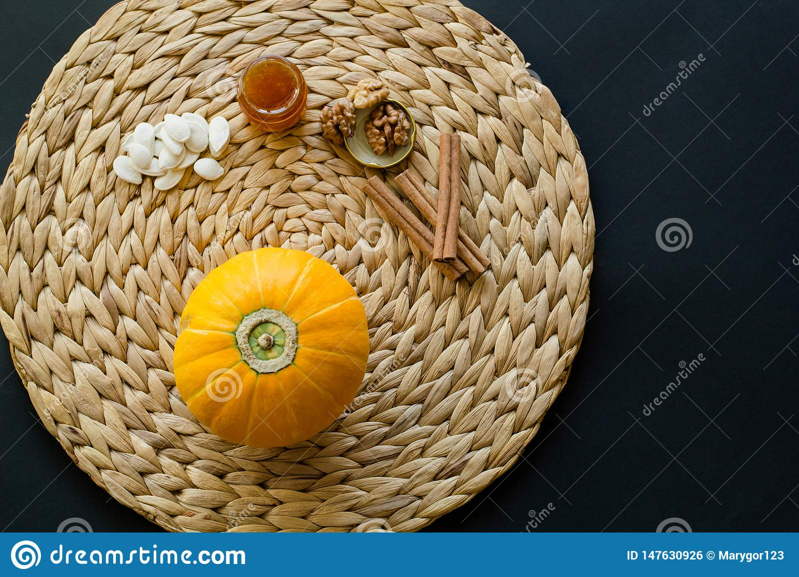 Small pumpkin with seeds, little glass can of honey, walnuts and cinnamon sticks on a circle mat/napkin made of water hyacinth on
