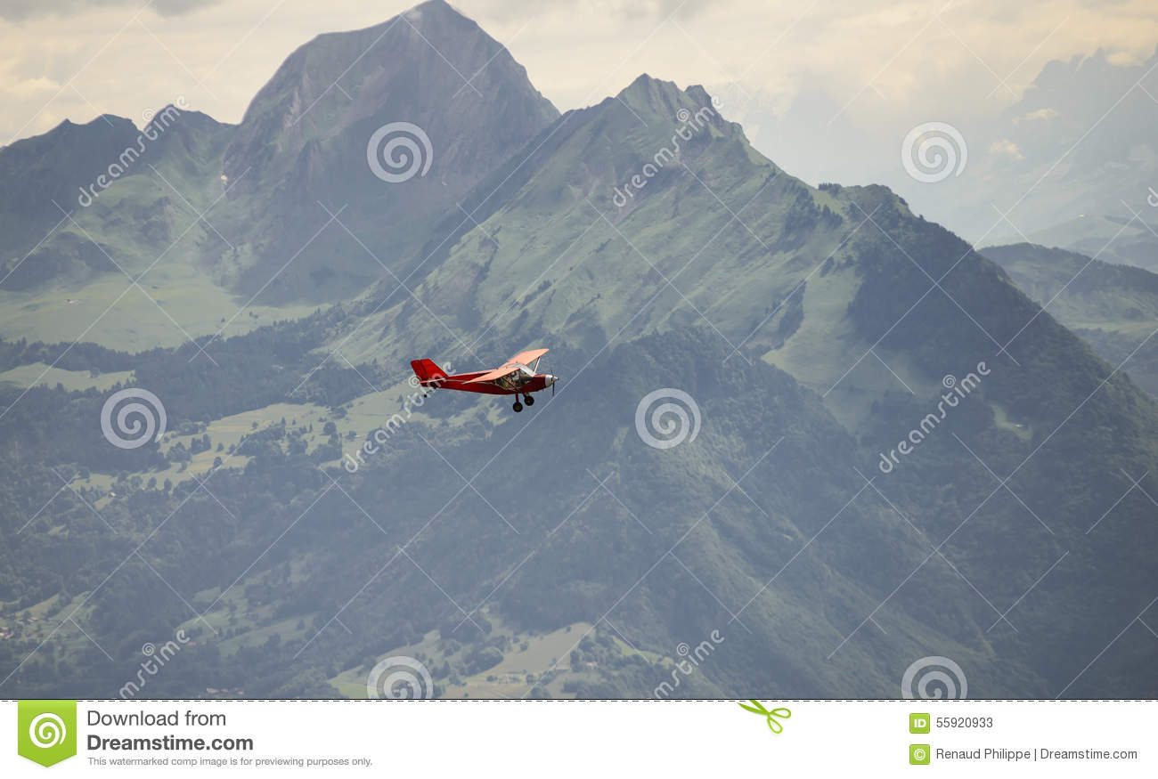A small red airplane flying over the Alps