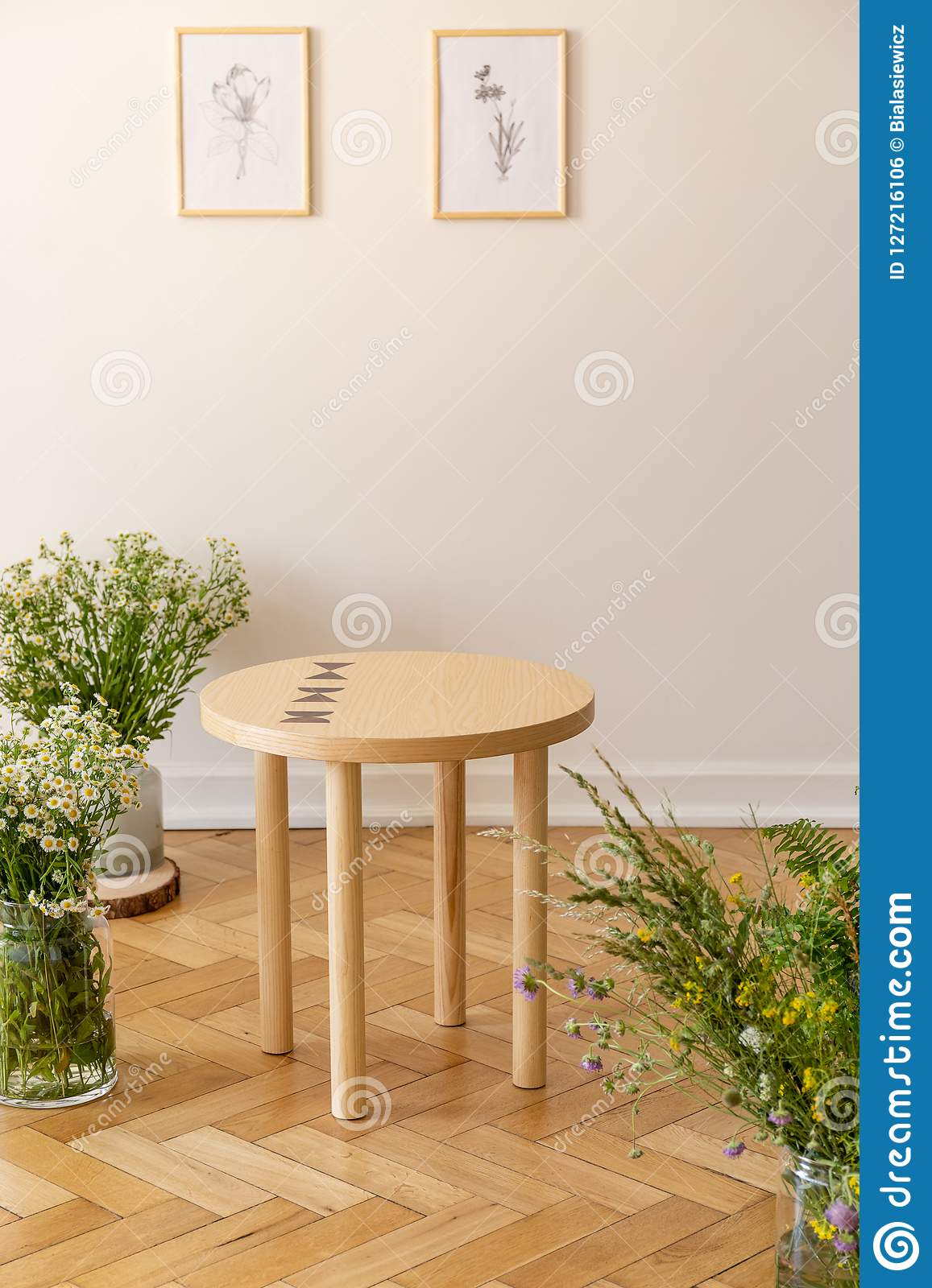 A small round wooden table surrounded by fresh meadow flowers standing on a parquet against a light beige wall with illustrations