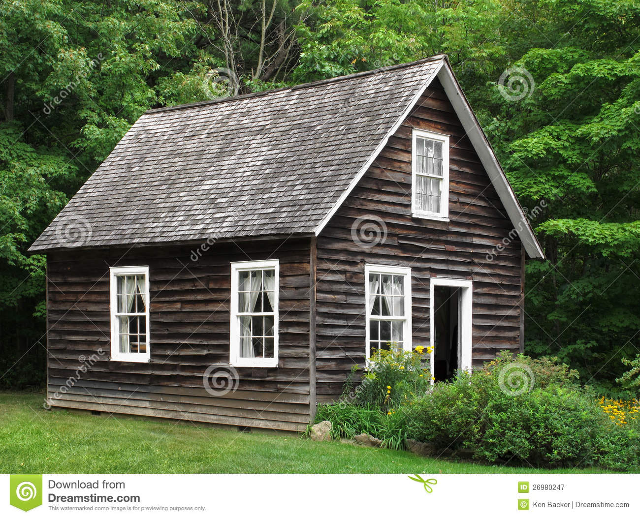 Small unpainted natural dark wood rustic house with trees and bushes