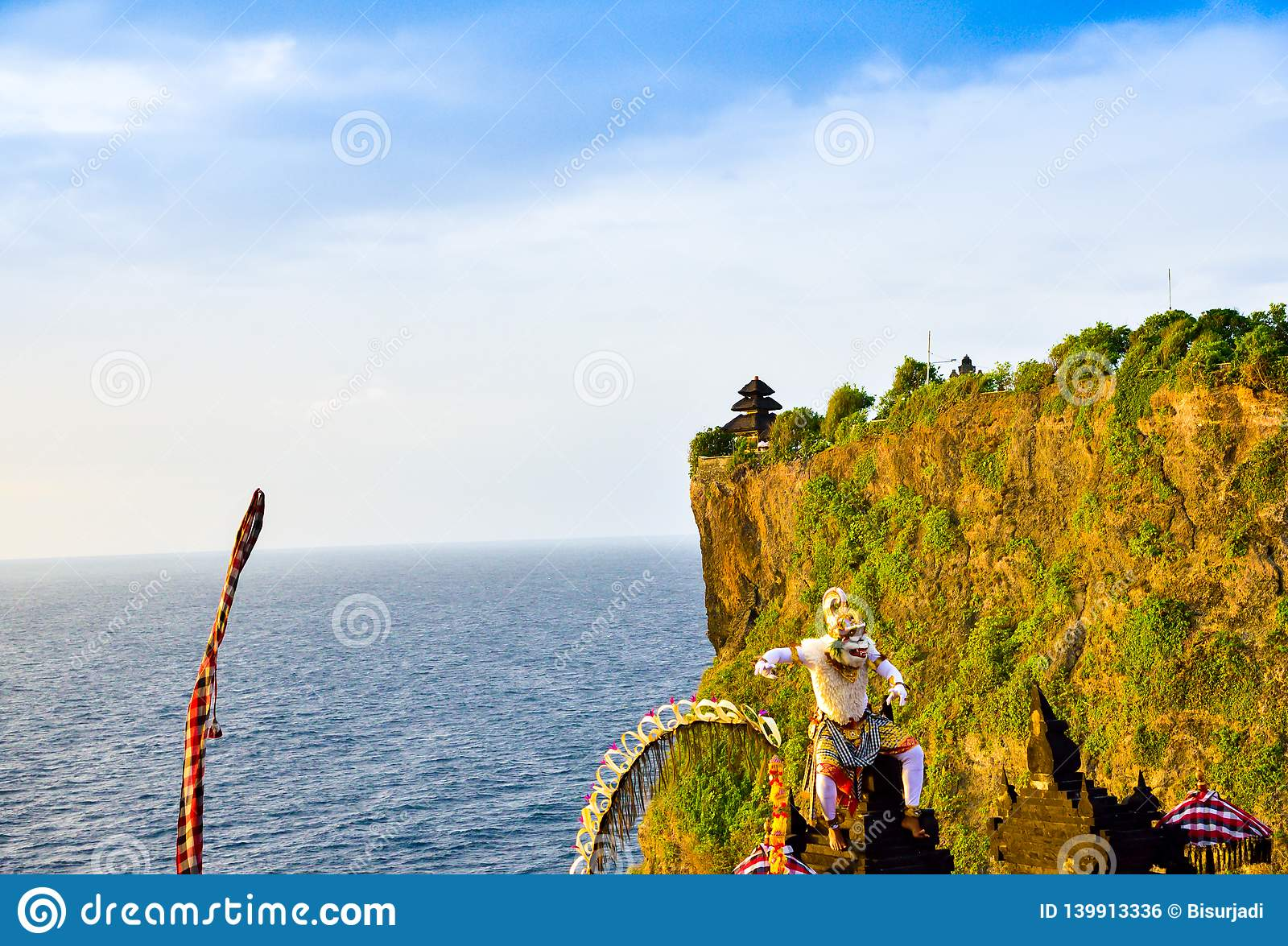 Goregeous romantic sunset at the cliff on top of the mountain with sacred temple on top and white monkey god character