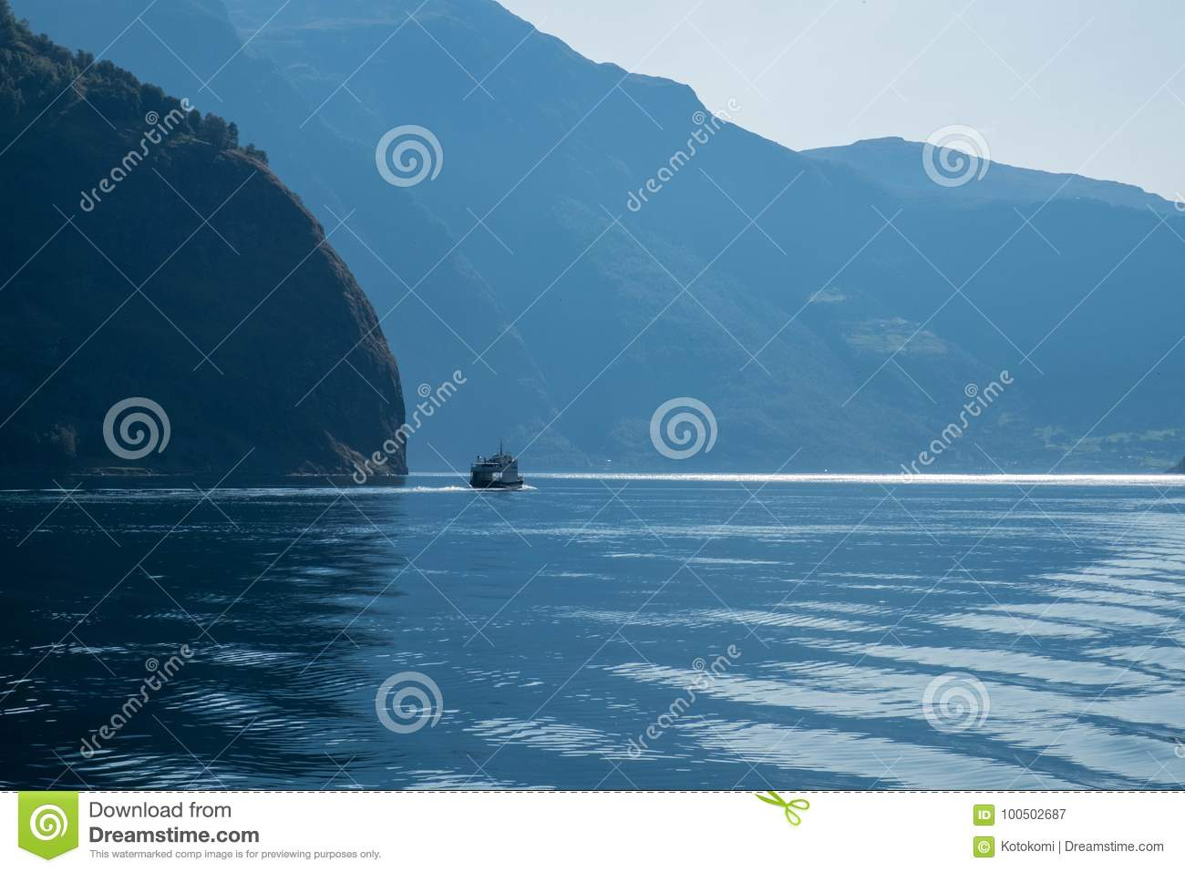 Small Ship Sails In Blue Water With Large Mountais  Norway