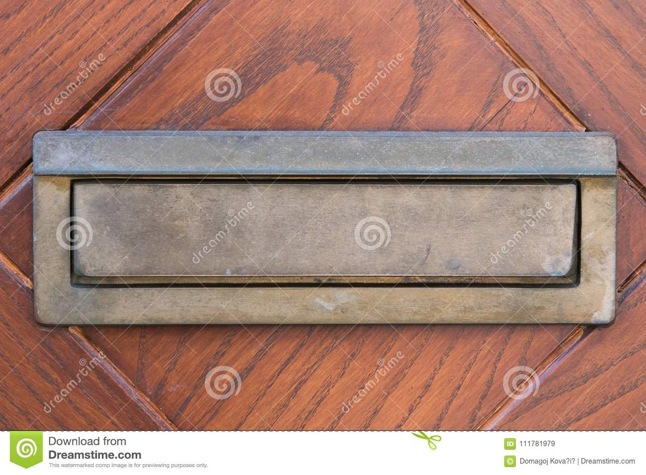 Small silver door mailbox on wooden doors. Small letterbox