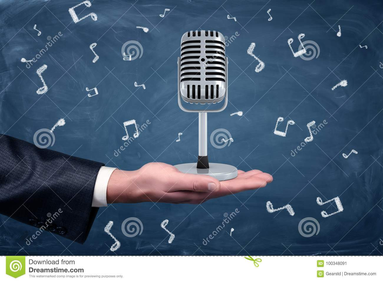 A small silver retro microphone standing on a businessman`s hand among music notes drawn on a blackboard background.