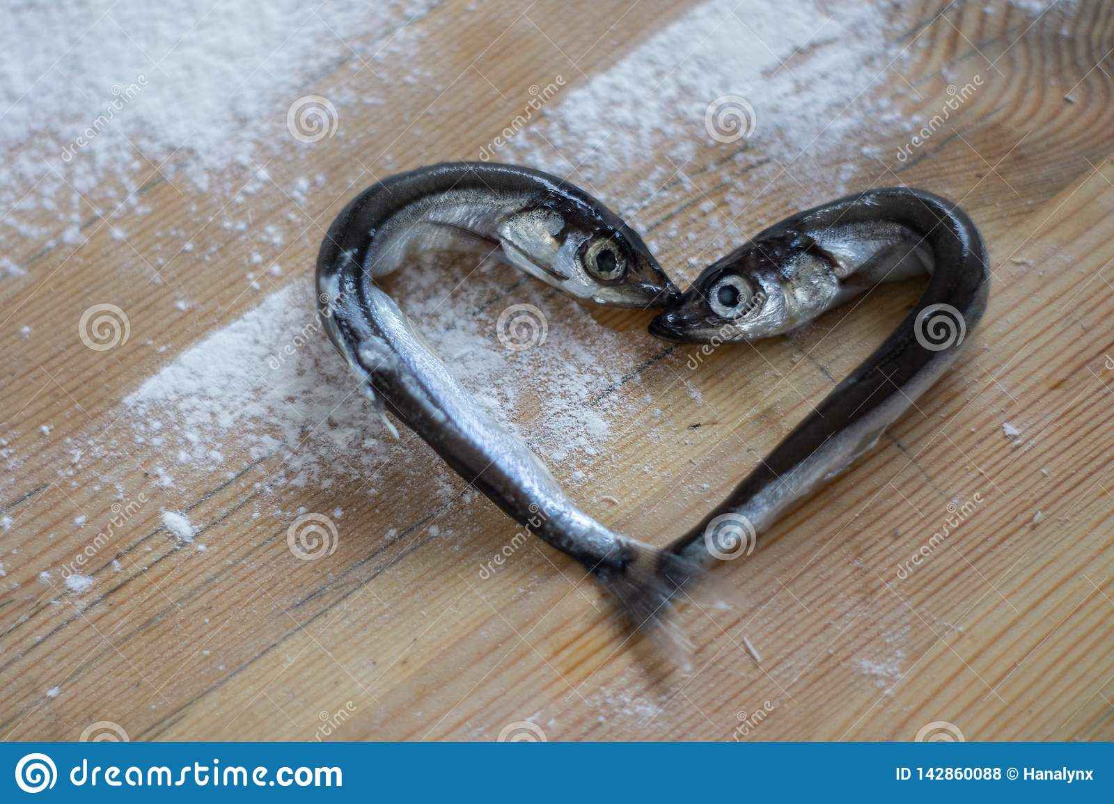 Small silver sea fish laid out in the shape of a heart