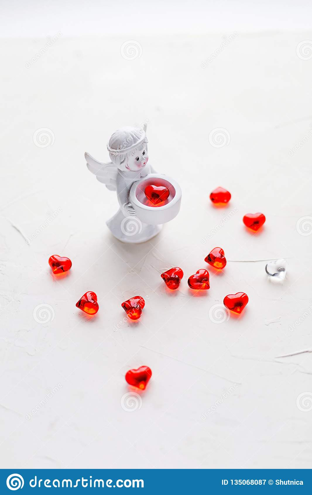 Small statuette of an angel on white with red hearts