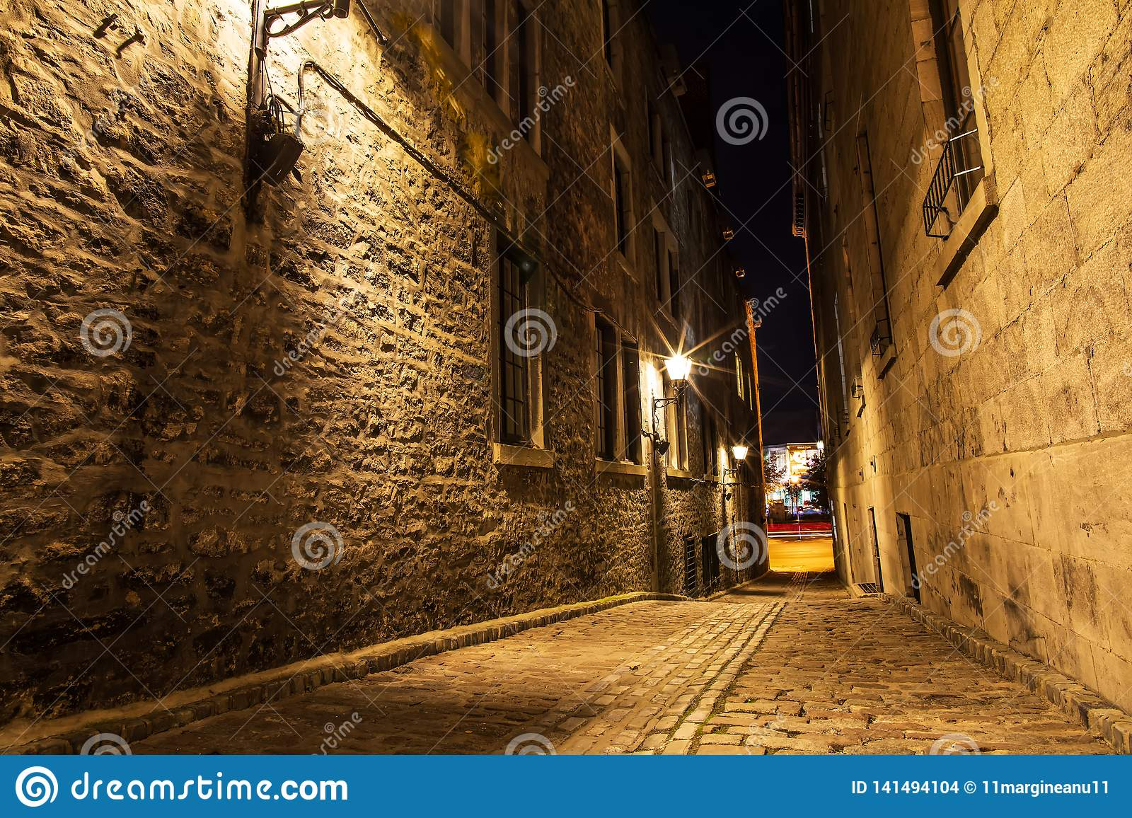 Small street and historical buildings in the historic site of Old Port from Montreal, night view. Scenic background of Canadian