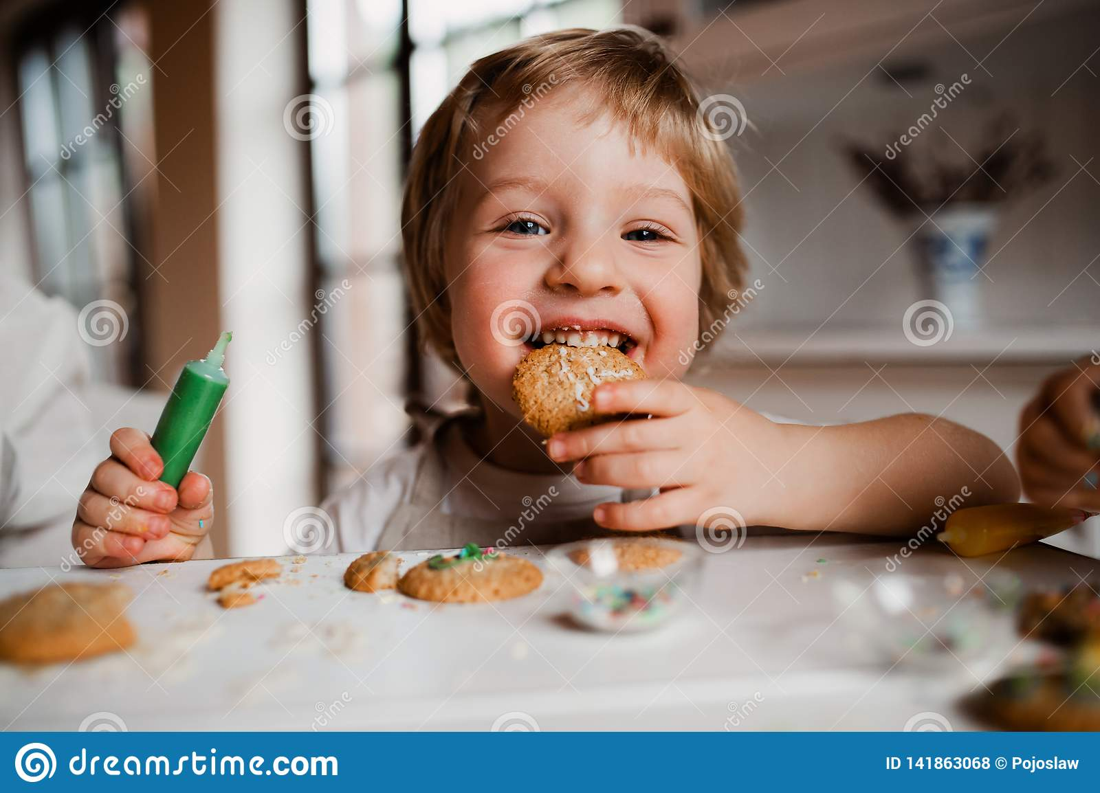 A small toddler boy sitting at the table, decorating and eating cakes at home.