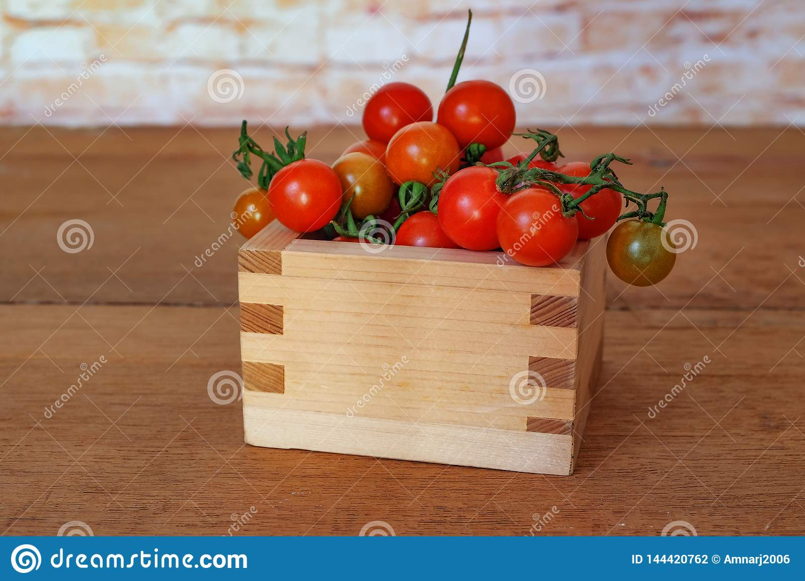 Small Tomato spill out of wood box.Food