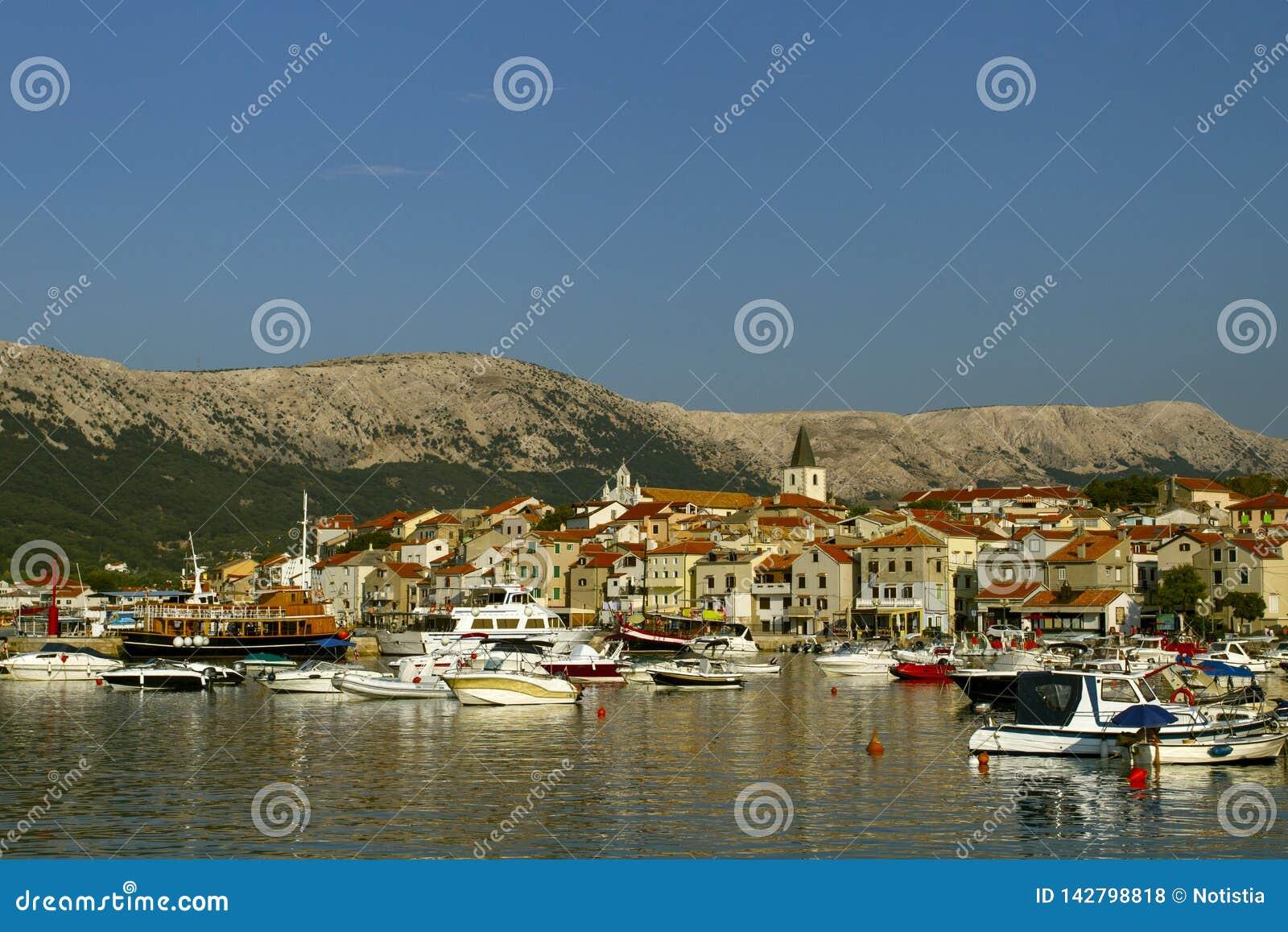 Small town of Baska its marina . Boat on foreground . Croatia vacation. Island Krk. Adriatic coast, Croatia, Europe. Summer vaca