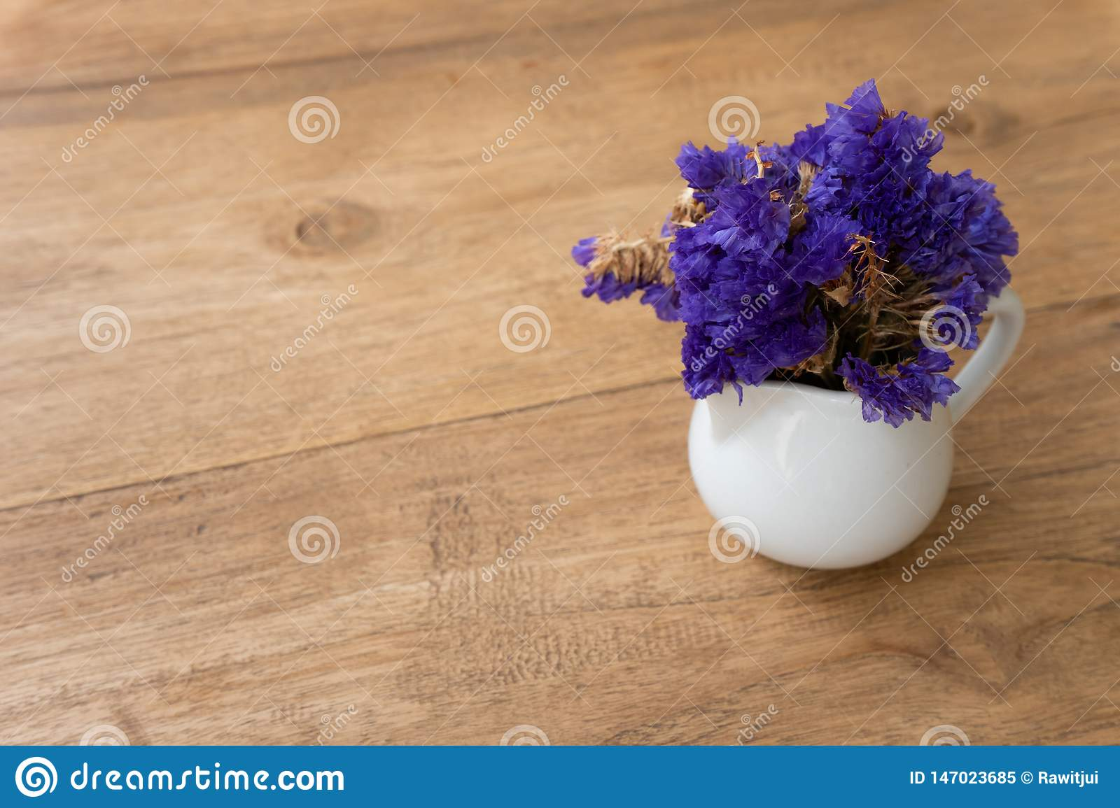 Small violet flower in a white cup on a wooden table