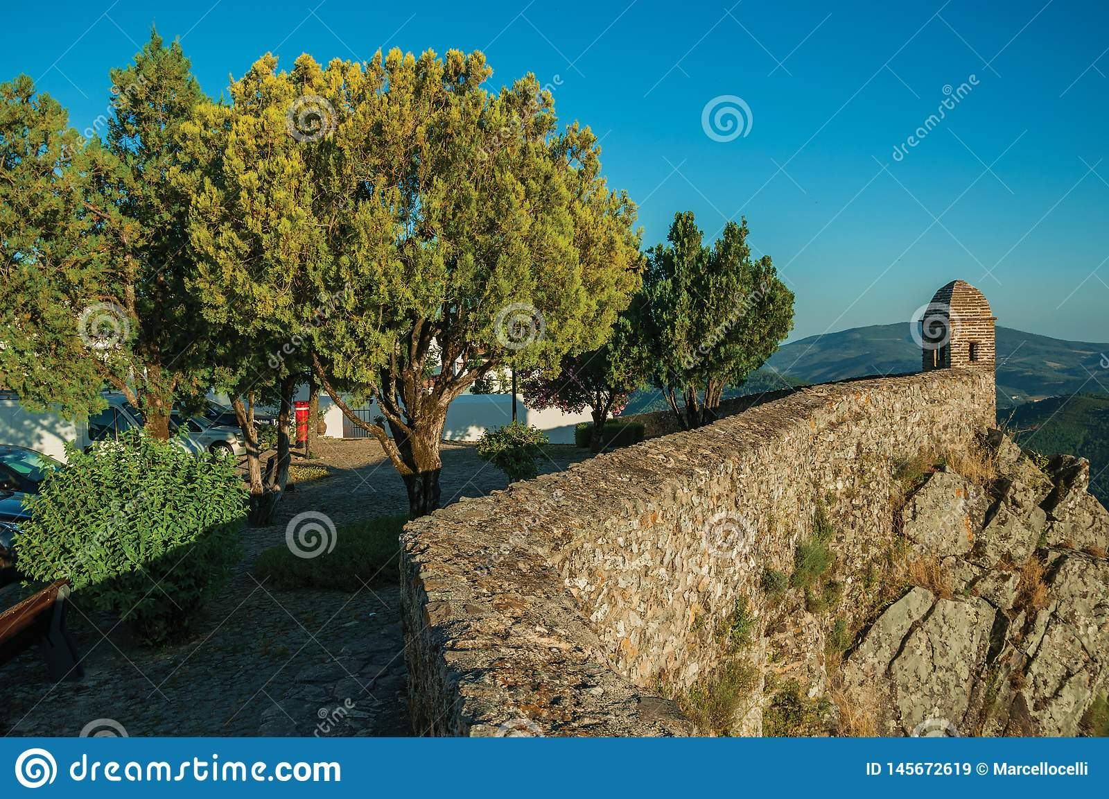 Small watchtower and stone wall over cliff with little wooden square