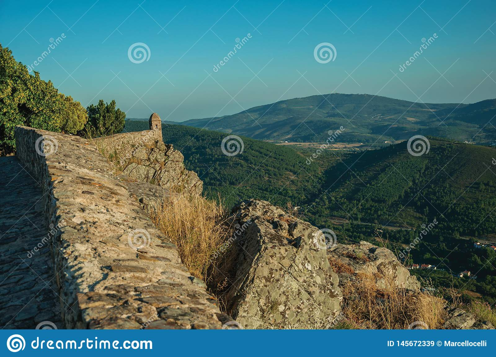 Small watchtower and stone wall over cliff with mountainous landscape