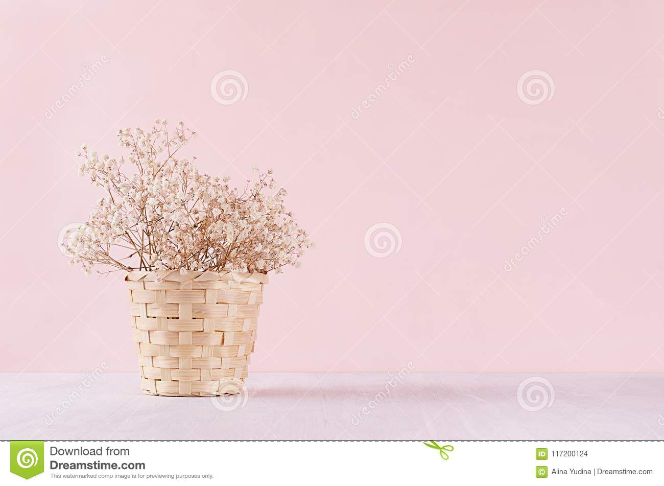Small white dried flowers in beige wicker basket on soft pink pastel background. Fresh light gentle background.