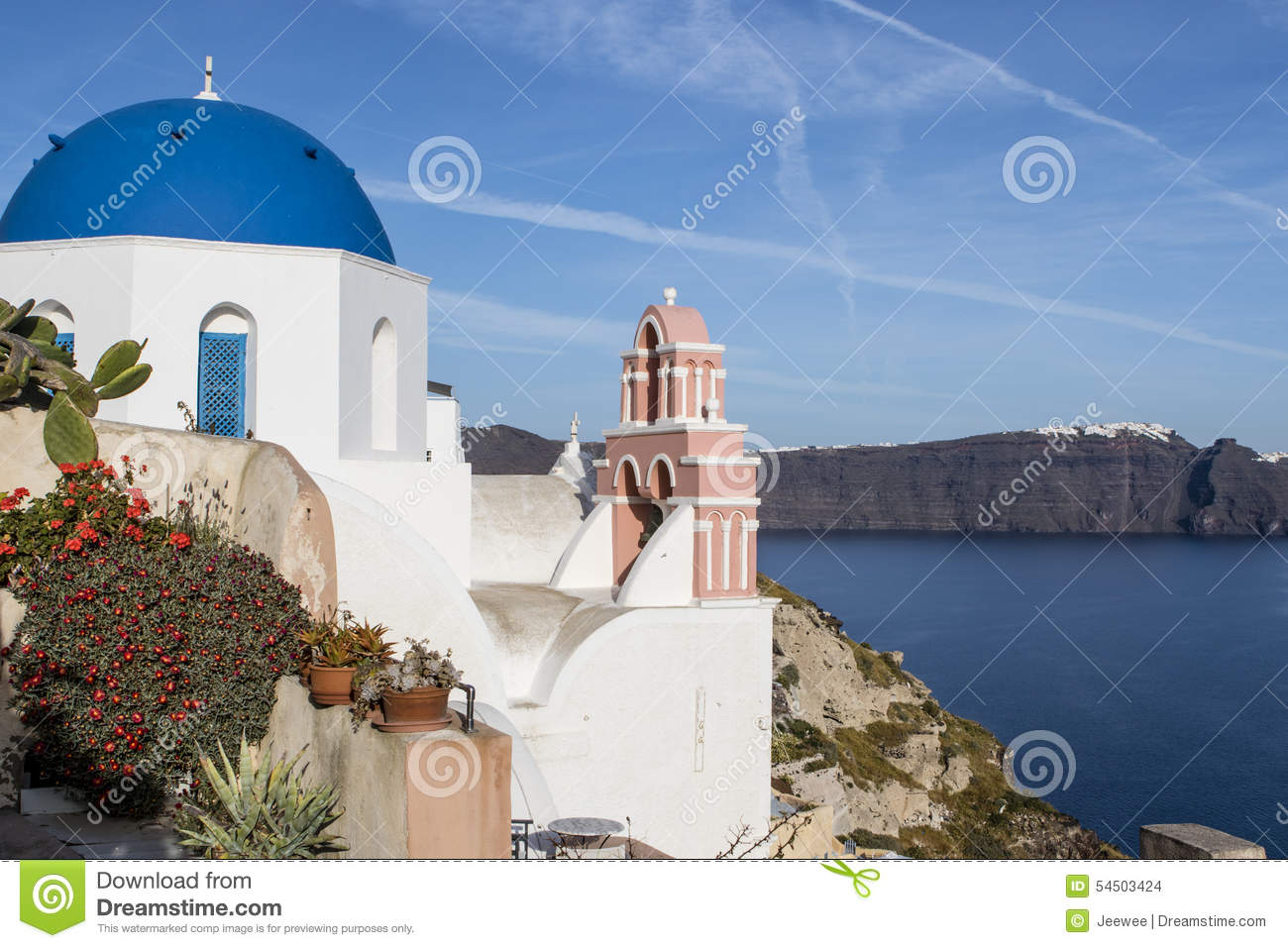 A small white Greek Orthodox church with a typical blue roof on the cliff in Oia, Santorini, Cyclades Greece