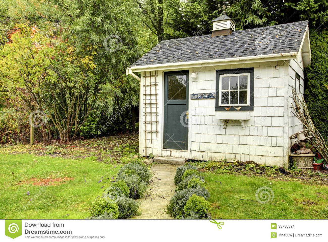 Small White Shed With Green Door And Window Stock Photo