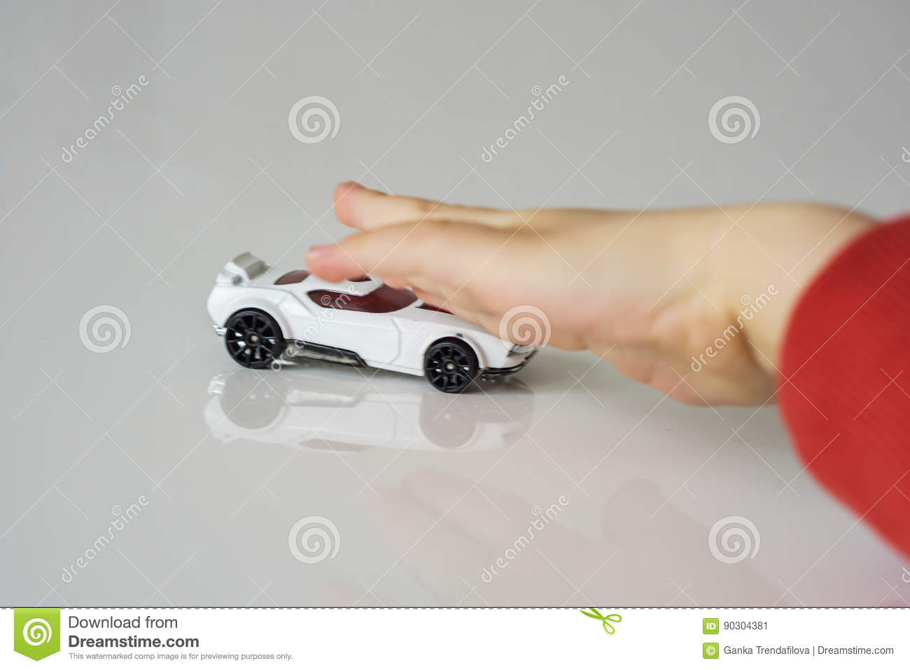 Small white toy car, pushed by children`s hand. The hand is defo